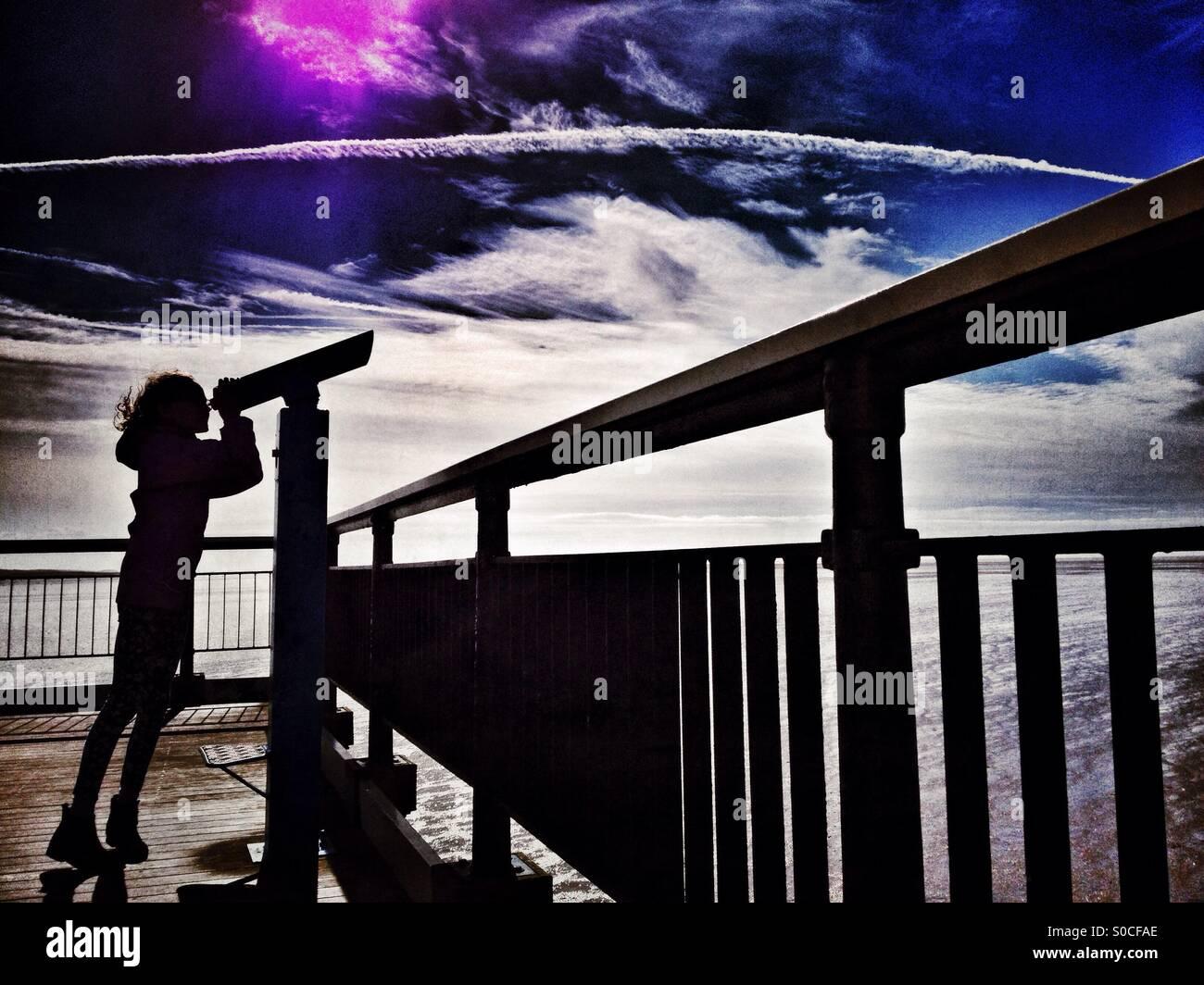 Junges Mädchen in der Silhouette mit Teleskop am Ende des Piers Stockbild