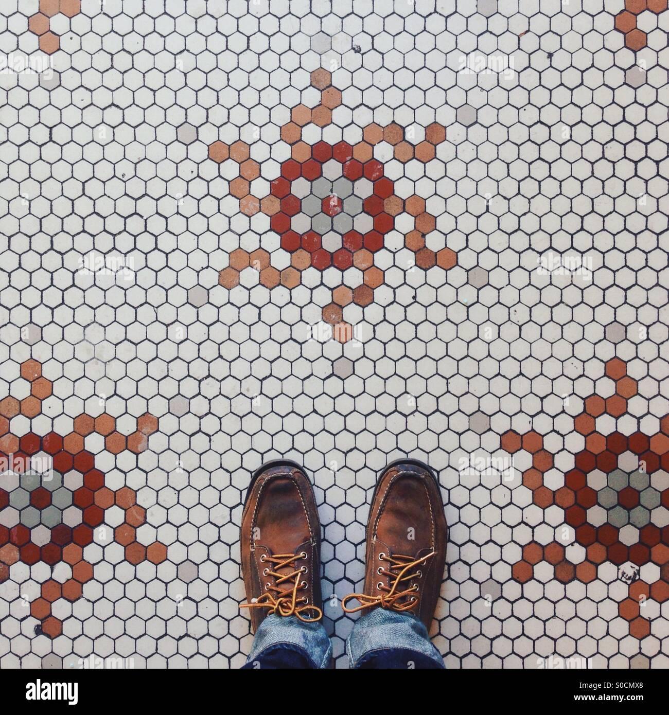 Fliesenboden und Füße Stockfoto