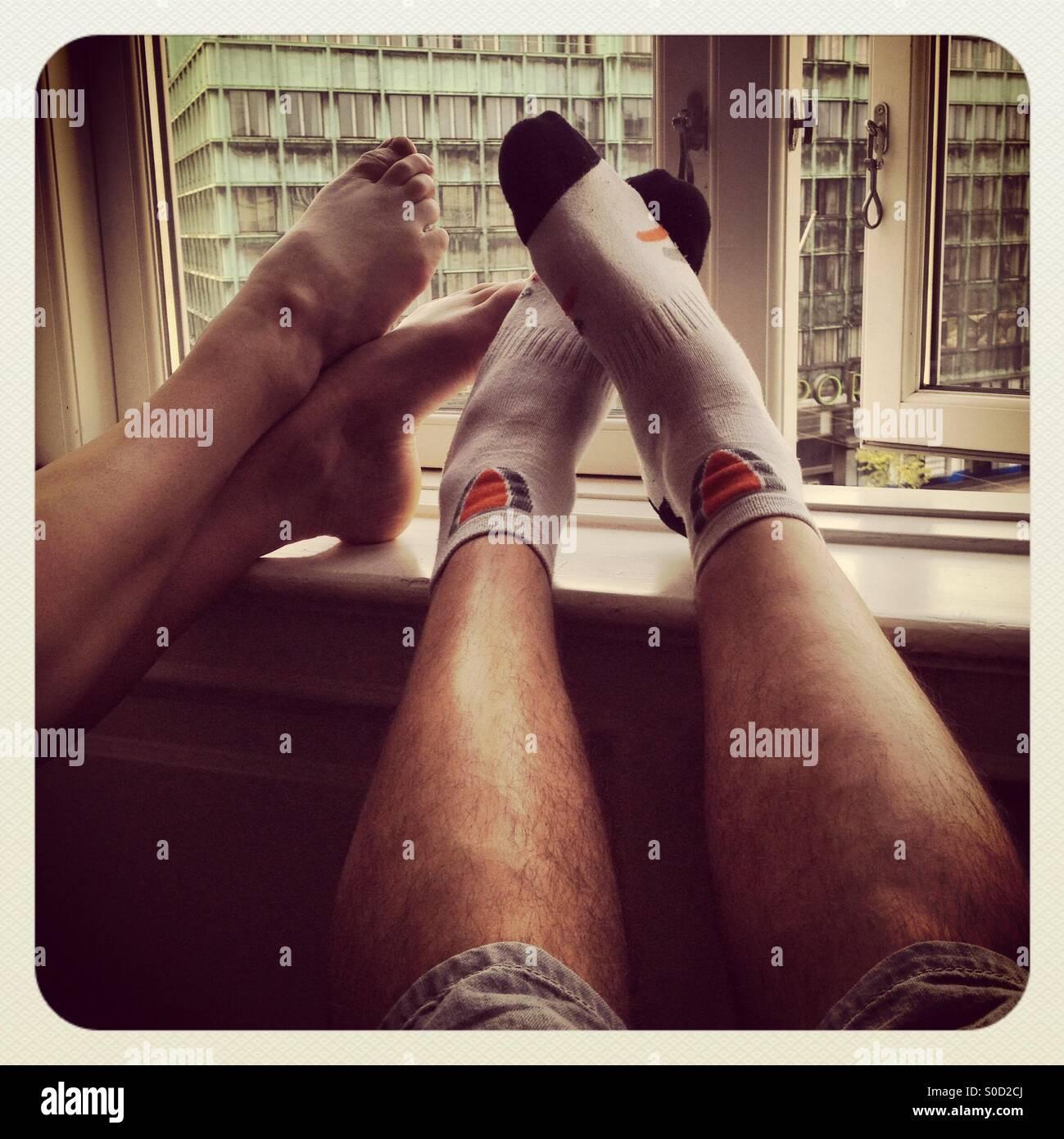 Ein paar ruhen die Füße auf einer Fensterbank Hotel in einem Hotel nach eines anstrengenden Tages zu Fuß Stockbild