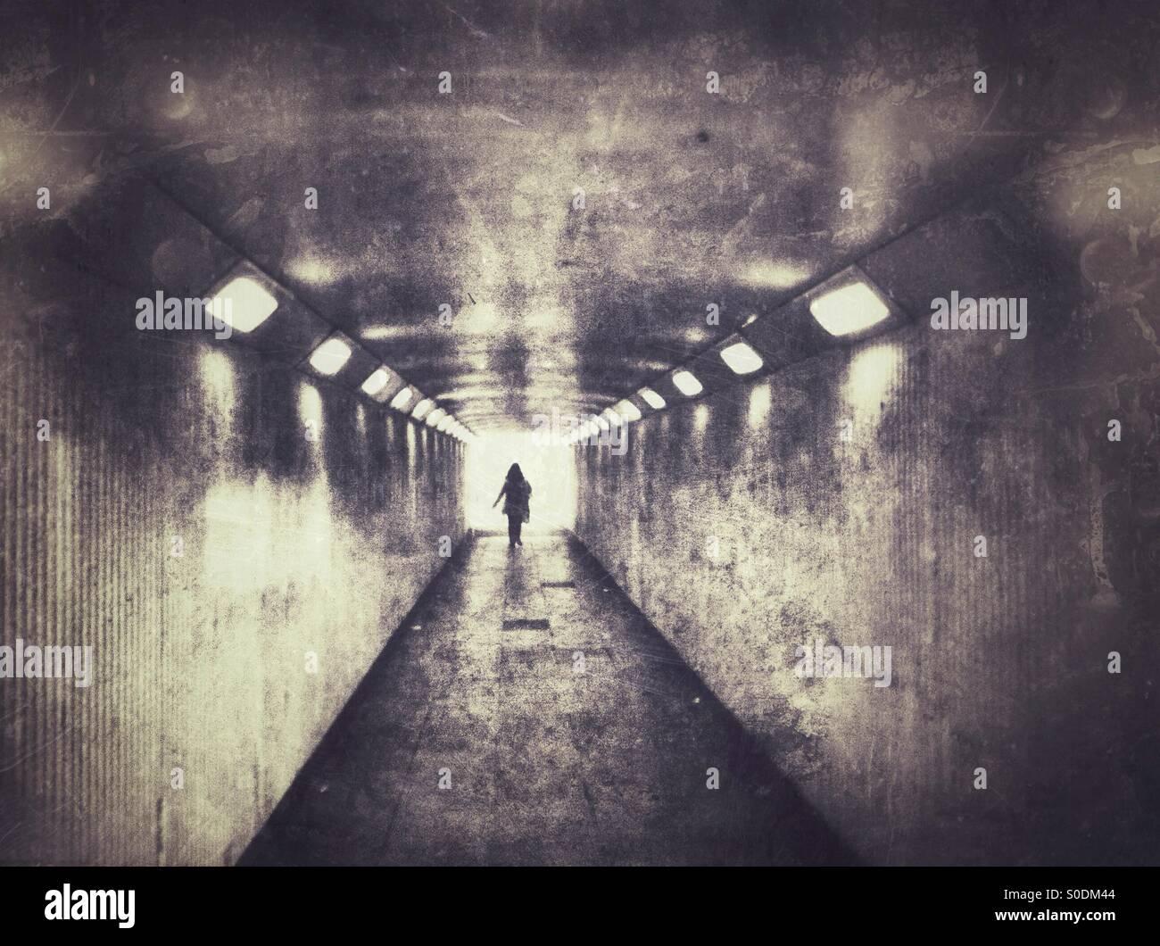 Einsame Frauen gehen in dunklen Unterführung. Stockbild