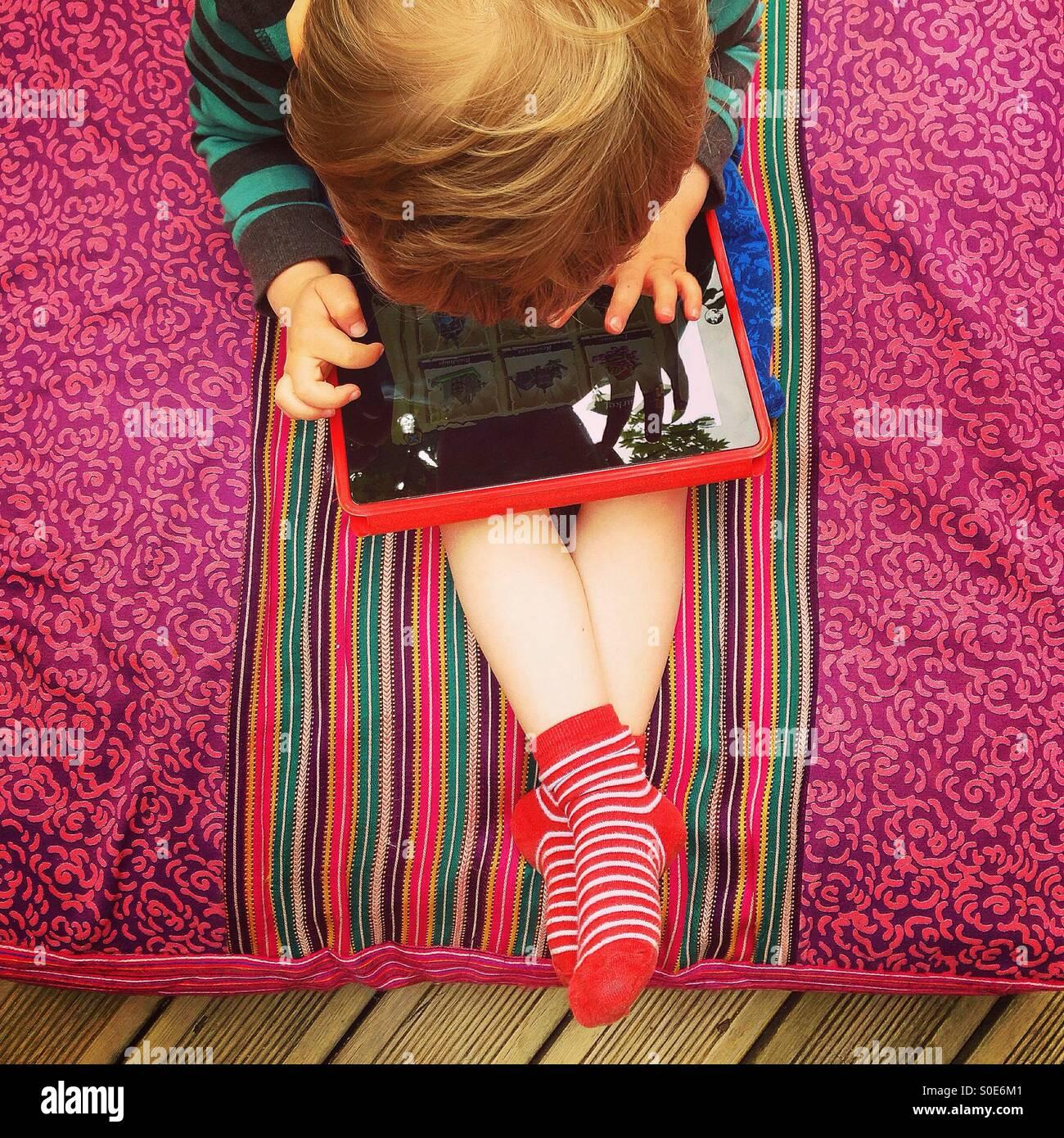 Young Boy spielen auf einem Tablet Stockbild