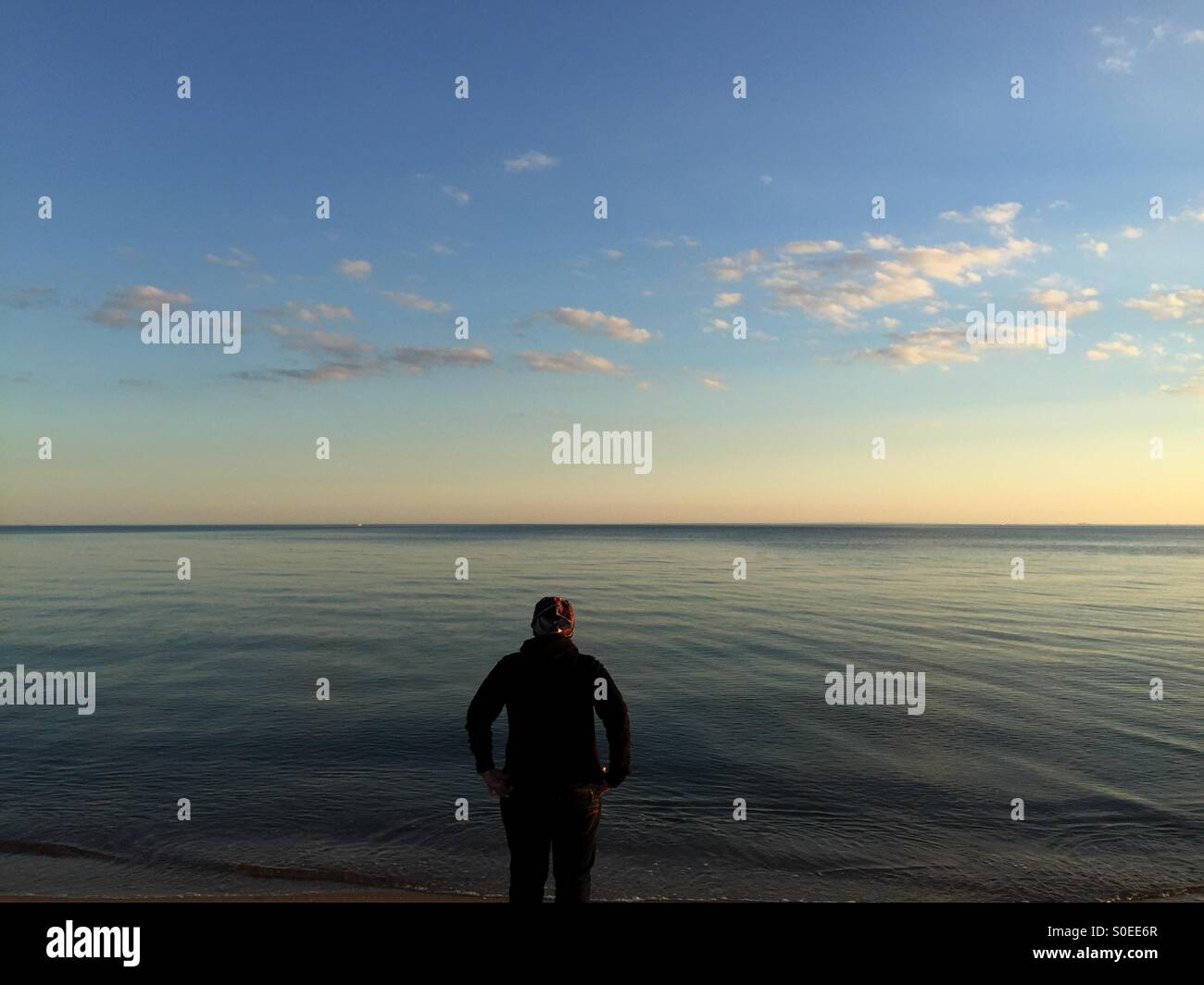 Steht man vor dem ruhigen Wasser Stockbild