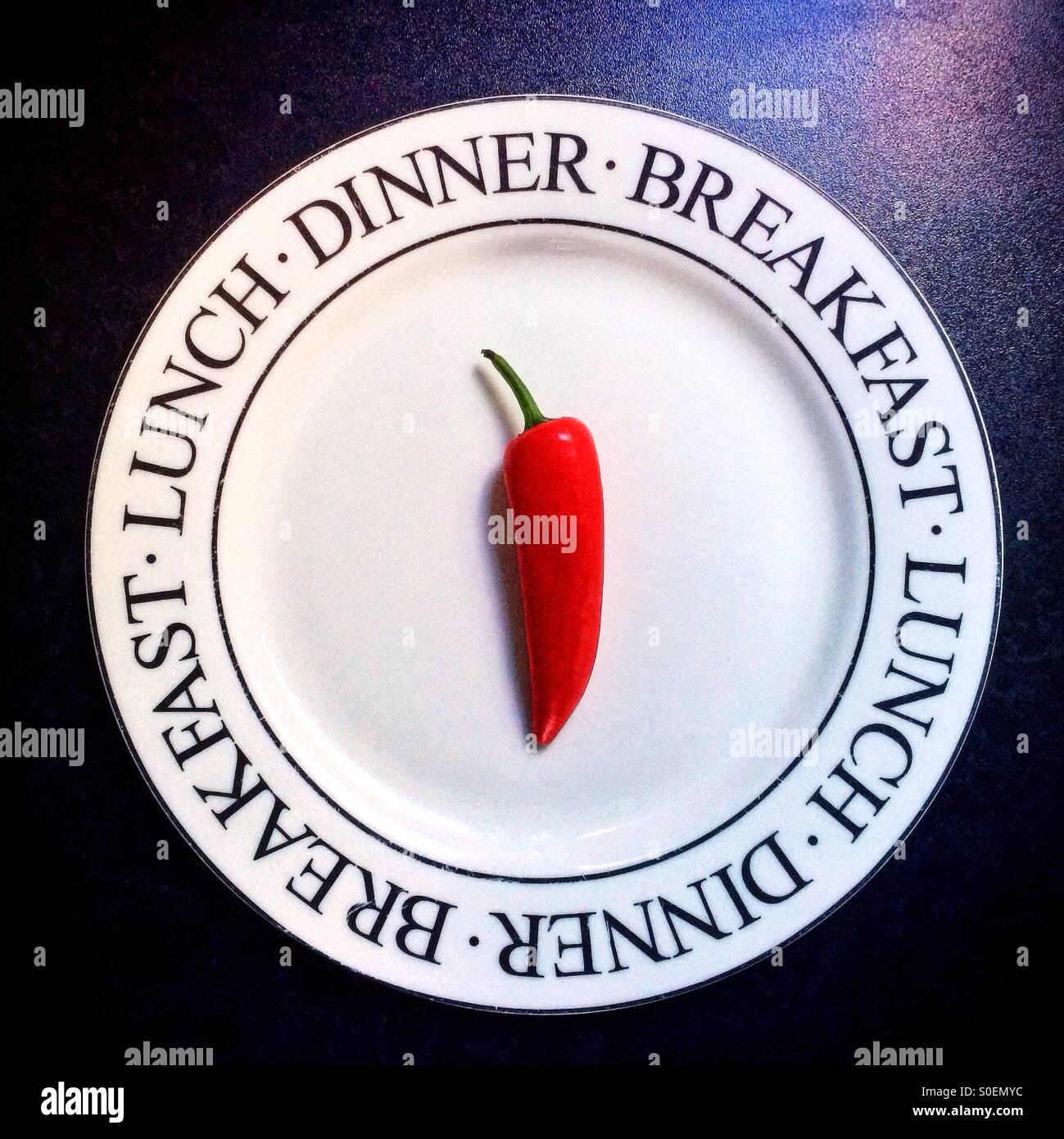 Eine einzelne rote Chilischote auf einem weißen Teller, dekoriert mit den Worten Frühstück, Mittag Stockbild
