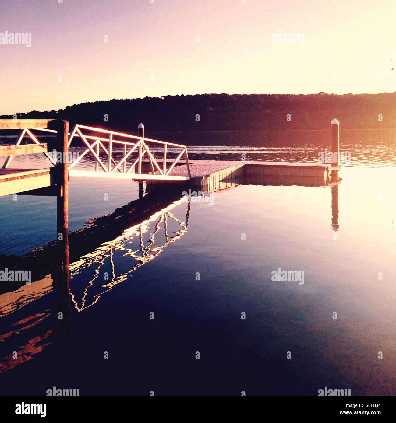 Ruhige See mit Steg und späten Nachmittagssonne Stockbild