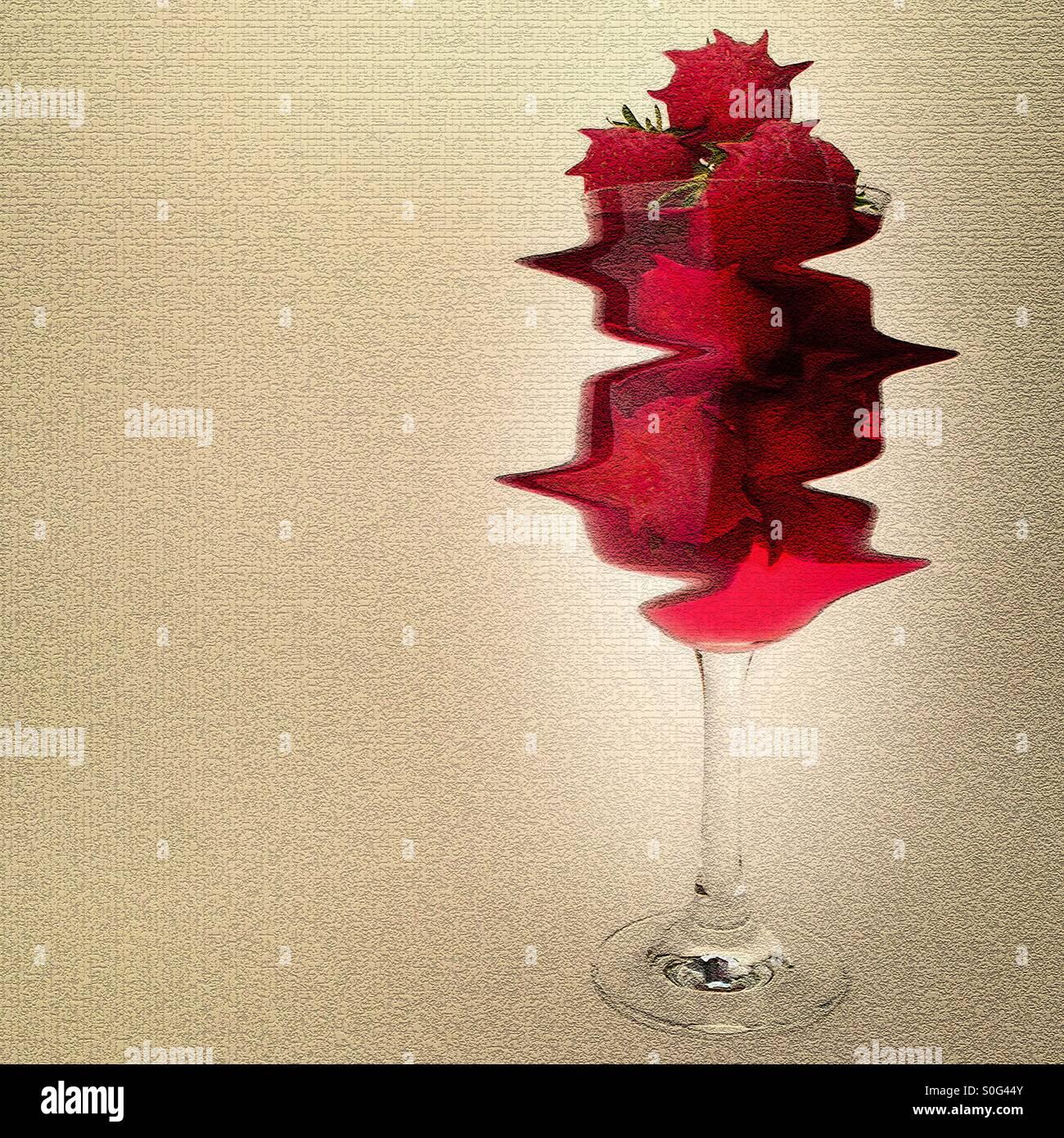 Erdbeeren und Saft in einem hohen Glas Wein Stockbild