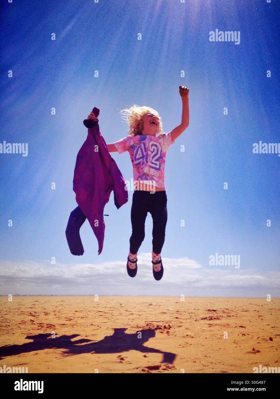 Junges Mädchen springen vor Freude am Strand Stockbild