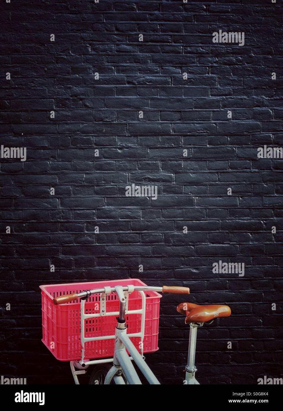 Weißen Fahrrad mit einem rosa Korb vor einer schwarzen Wand Stockbild