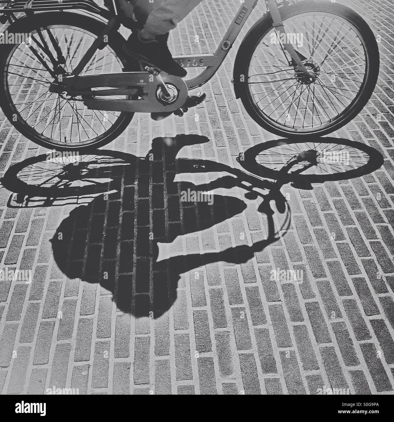 Einen vorbeifahrenden Radfahrer Schatten Stockbild