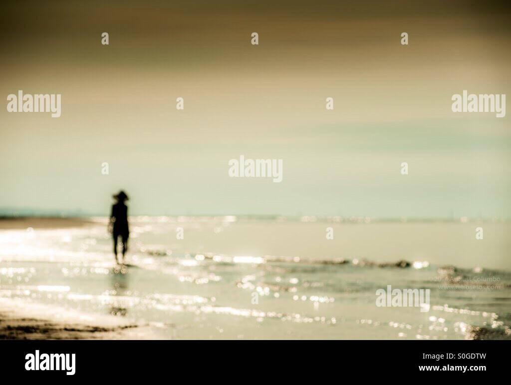 Eine Figur der Frau alleine am Meer Stockbild