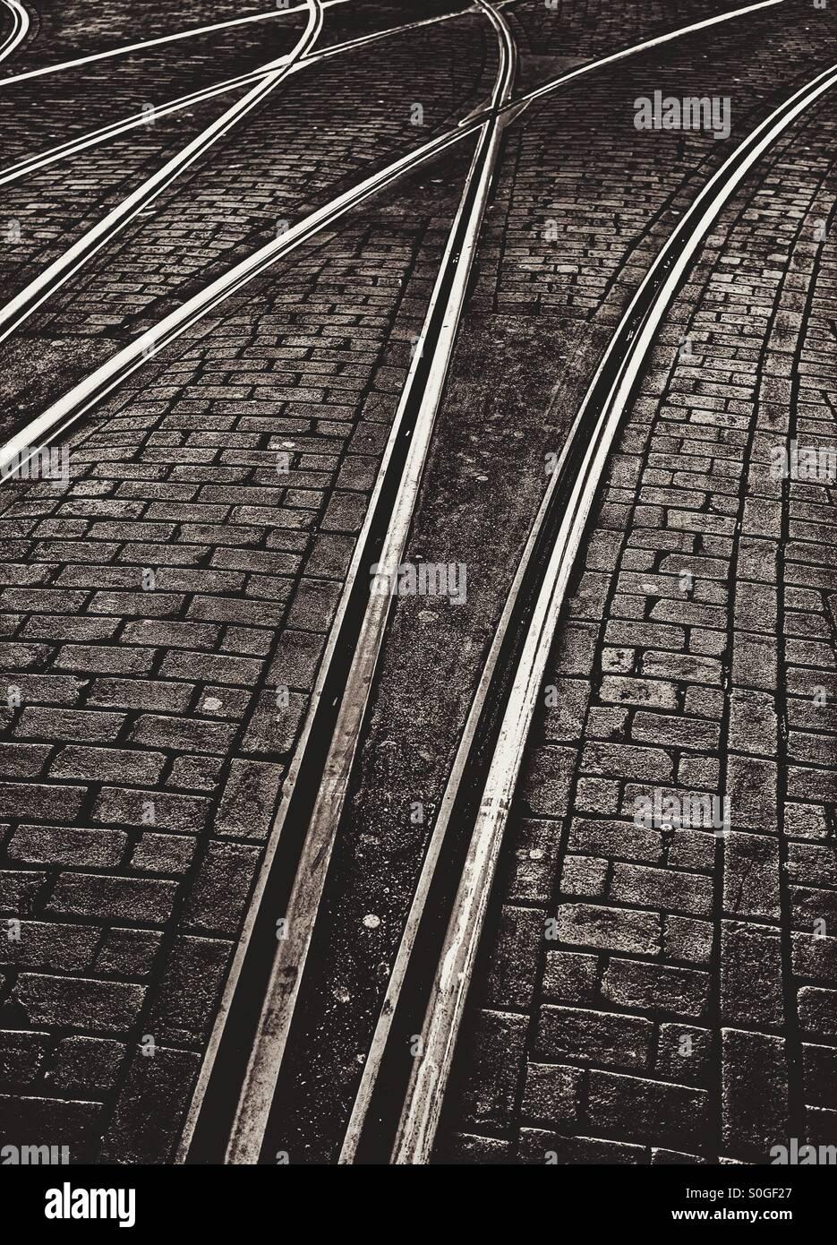 Straßenbahnlinien auf einer alten gepflasterten Straße Stockbild