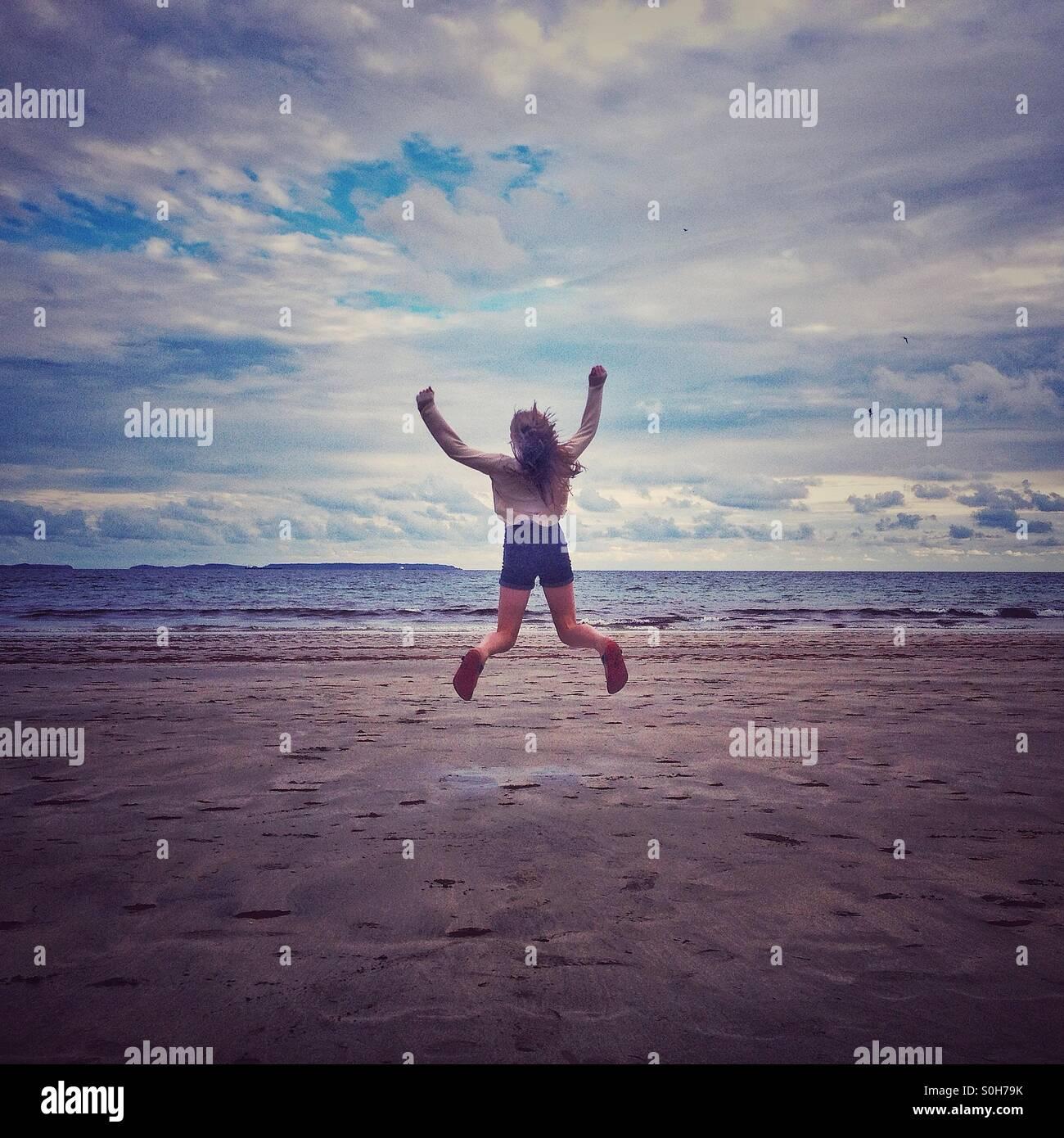 Mädchen am Strand springen Stockbild