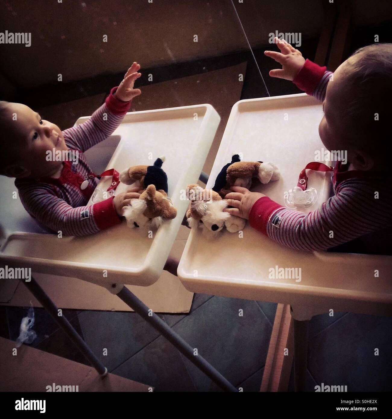 Baby Junge spielt mit seinem Spiegelbild Stockbild