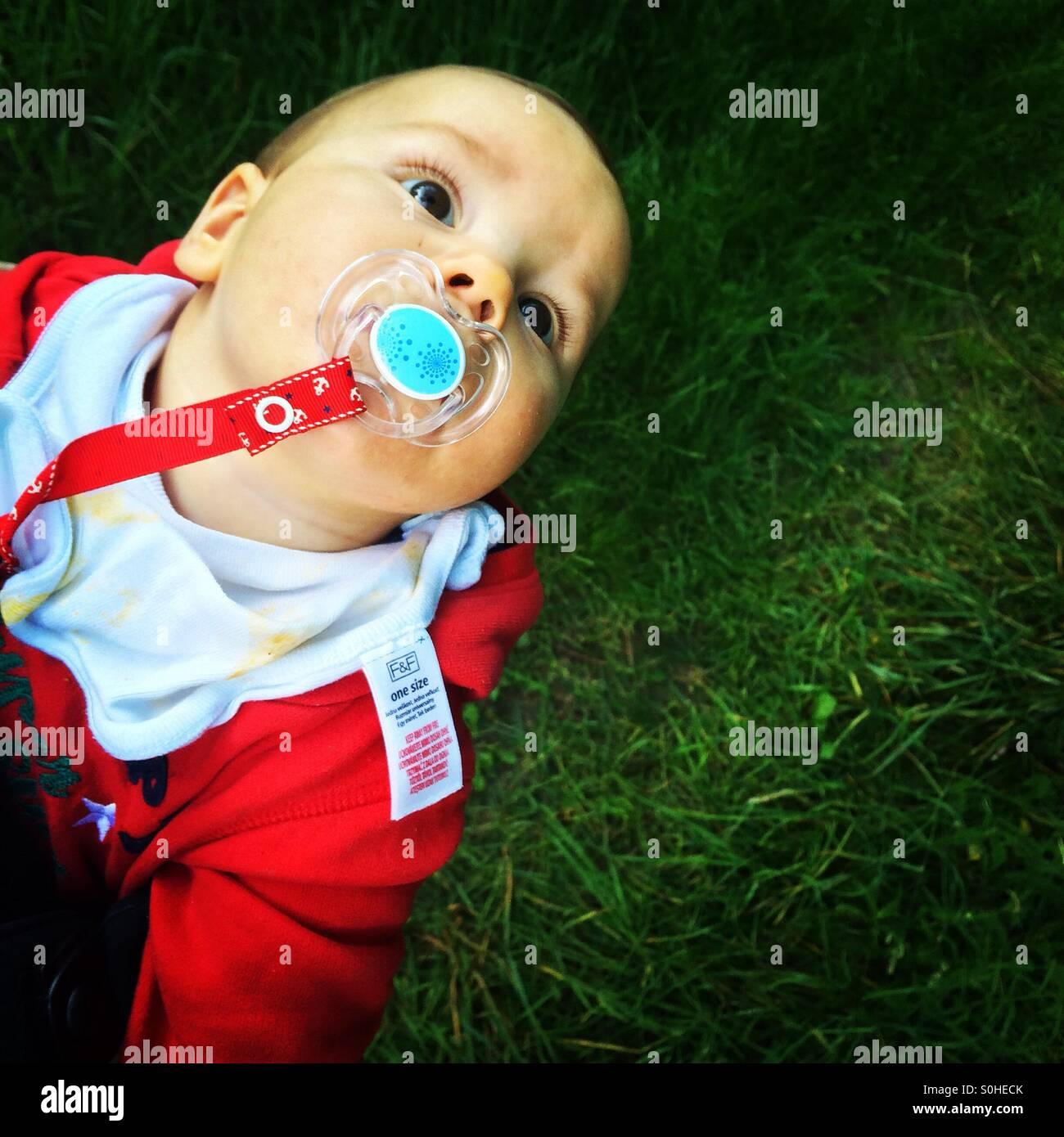 Baby Boy mit einem Schnuller nachschlagen Stockbild