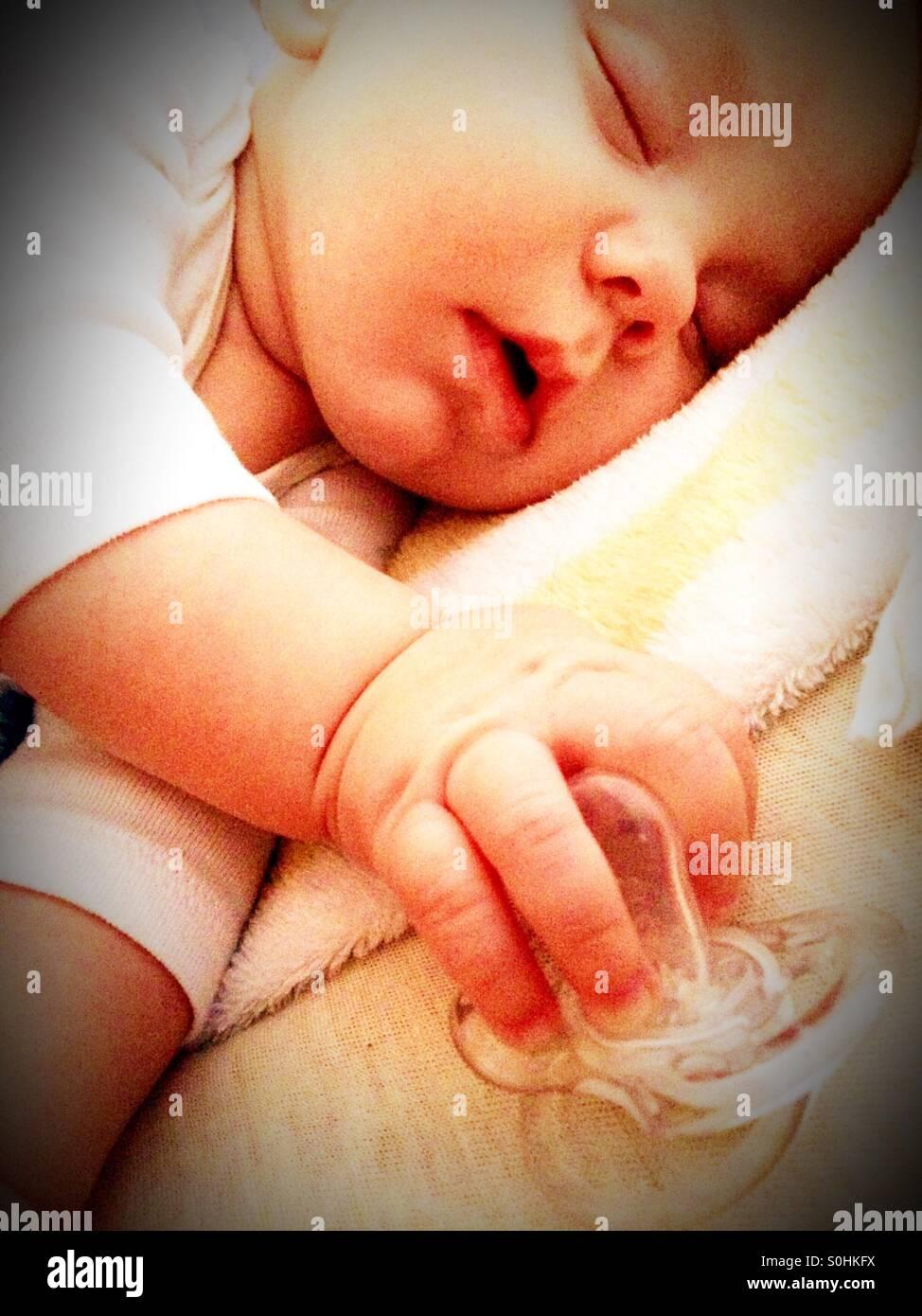 Schlafenden Baby Boy hält seinen Schnuller Stockfoto