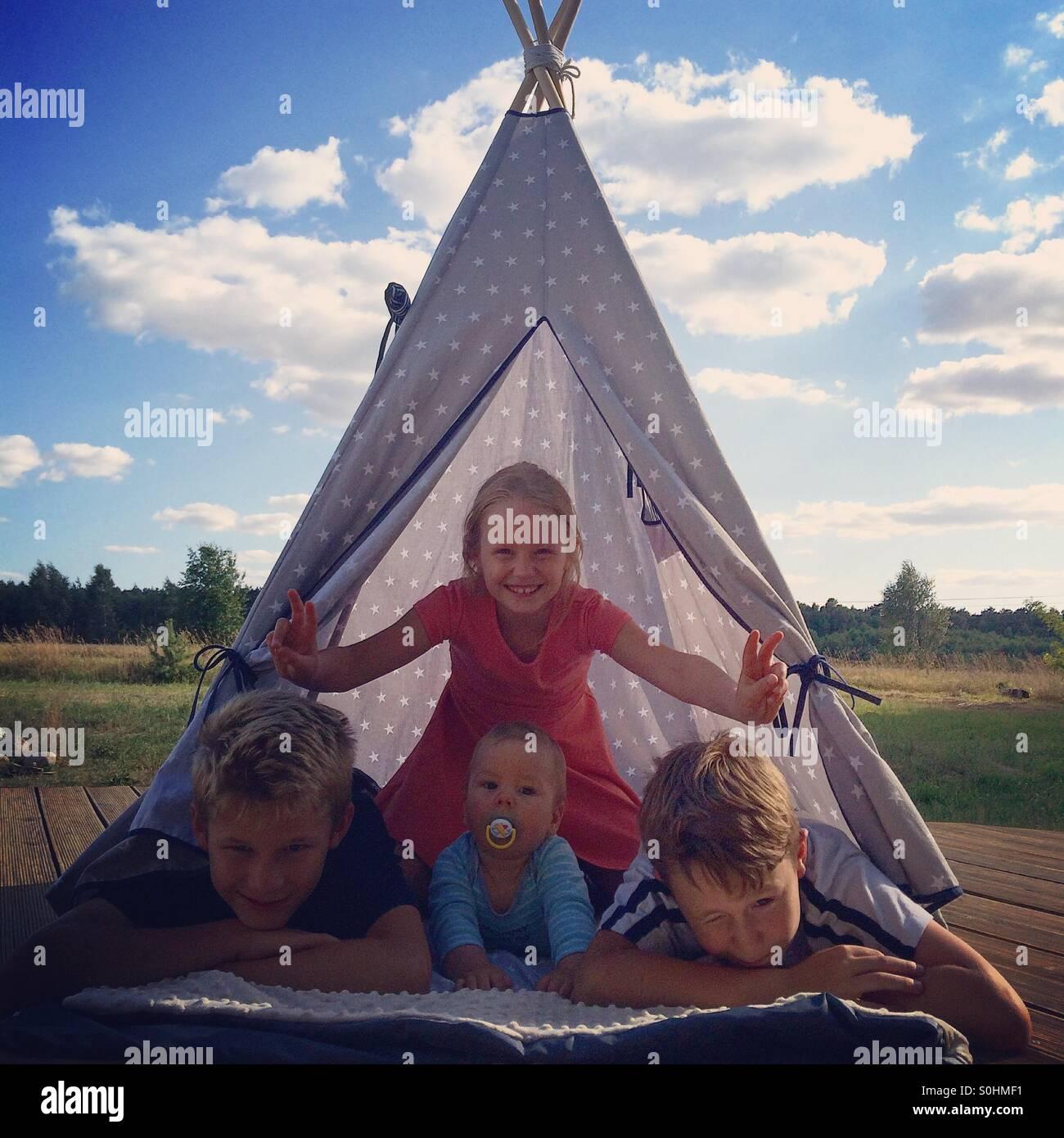 Vier Geschwister gemeinsam im Tipi an heißen Sommertag Stockbild