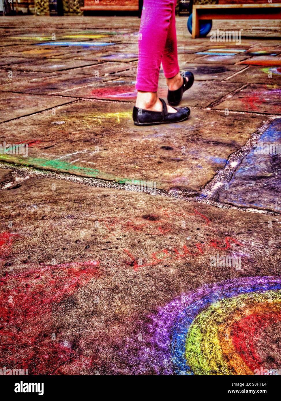 Junge Mädchen zu Fuß auf Pflaster bedeckt mit Kreidezeichnungen des Kindes Stockbild