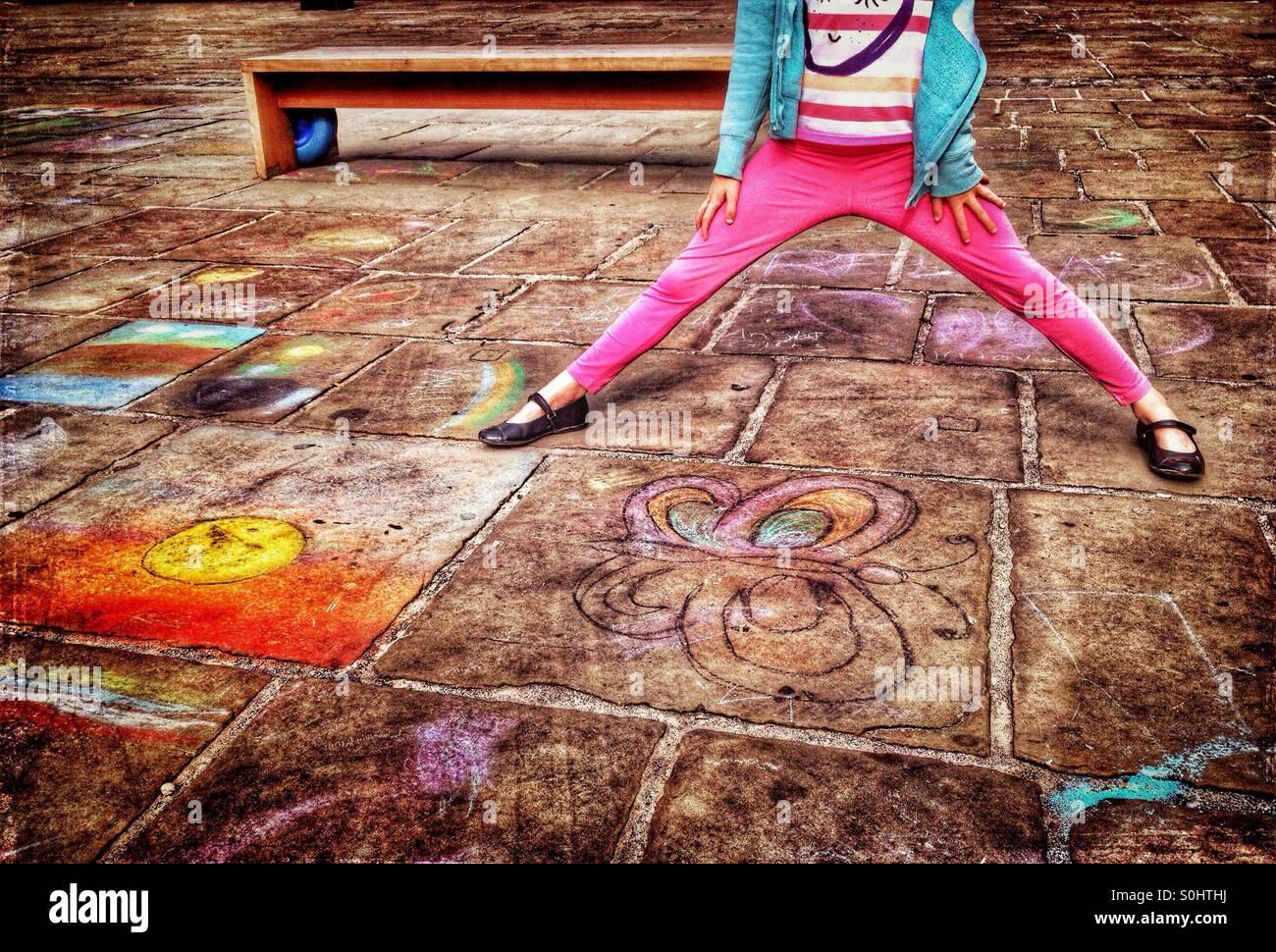 Junge Mädchen stehen auf Pflaster bedeckt Kreidezeichnungen Stockbild