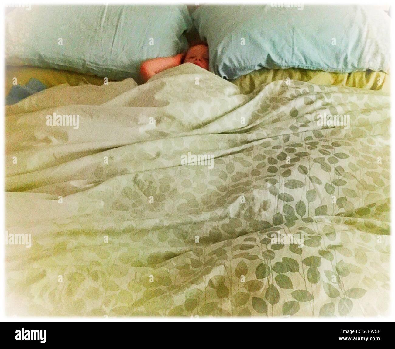 Kleines Kind in einem großen Bett schlafen Stockbild
