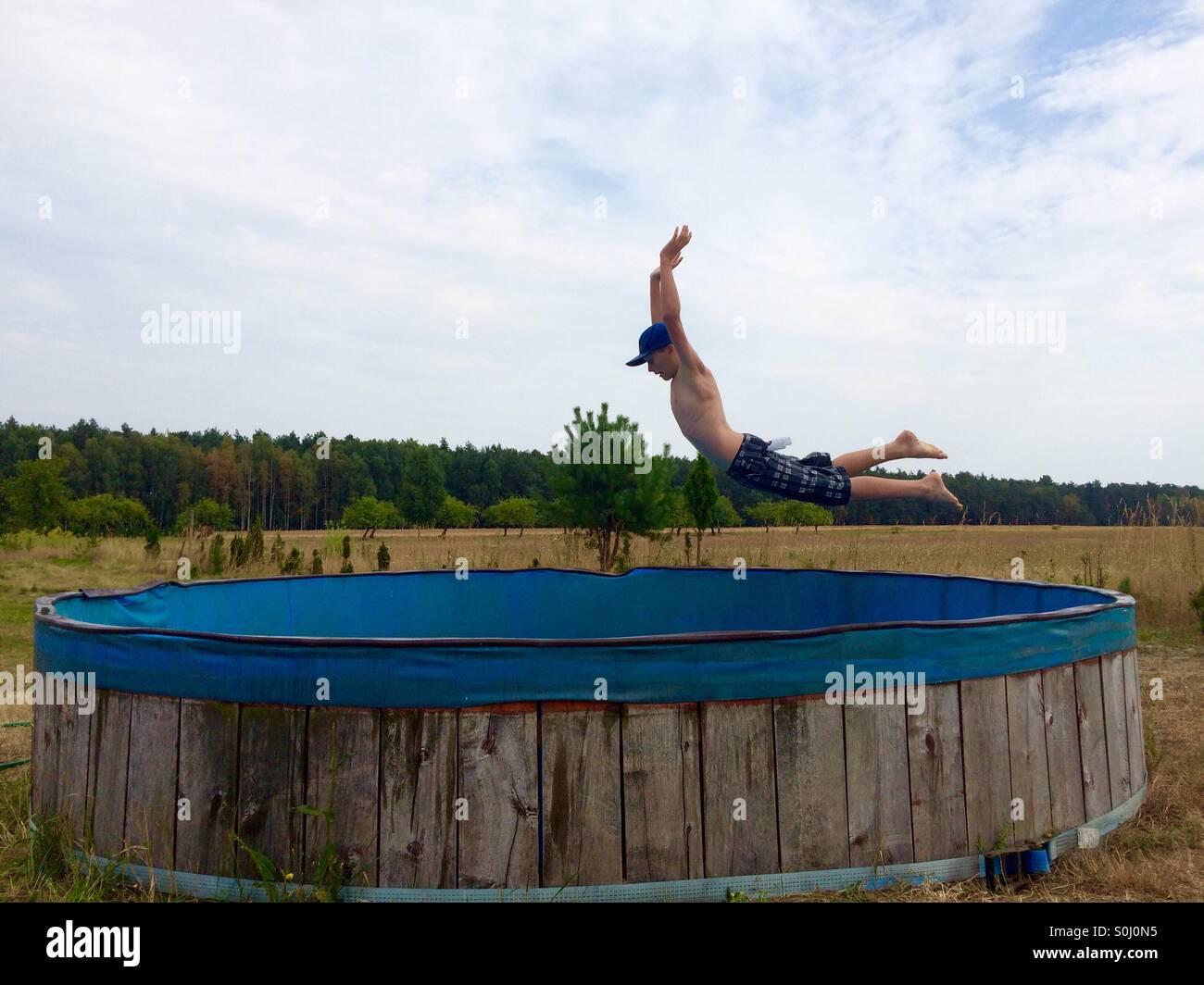 Teenager springt in seinem Swimmingpool von der Feld-Hof Stockbild