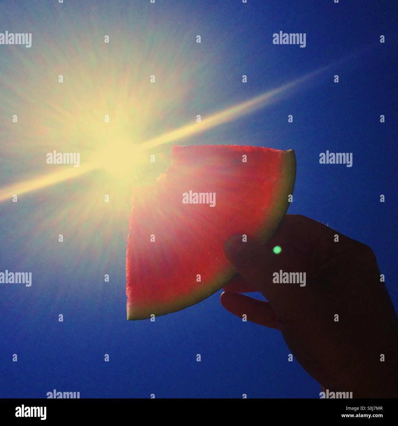 Wassermelone in der Sonne aufgehalten Stockbild