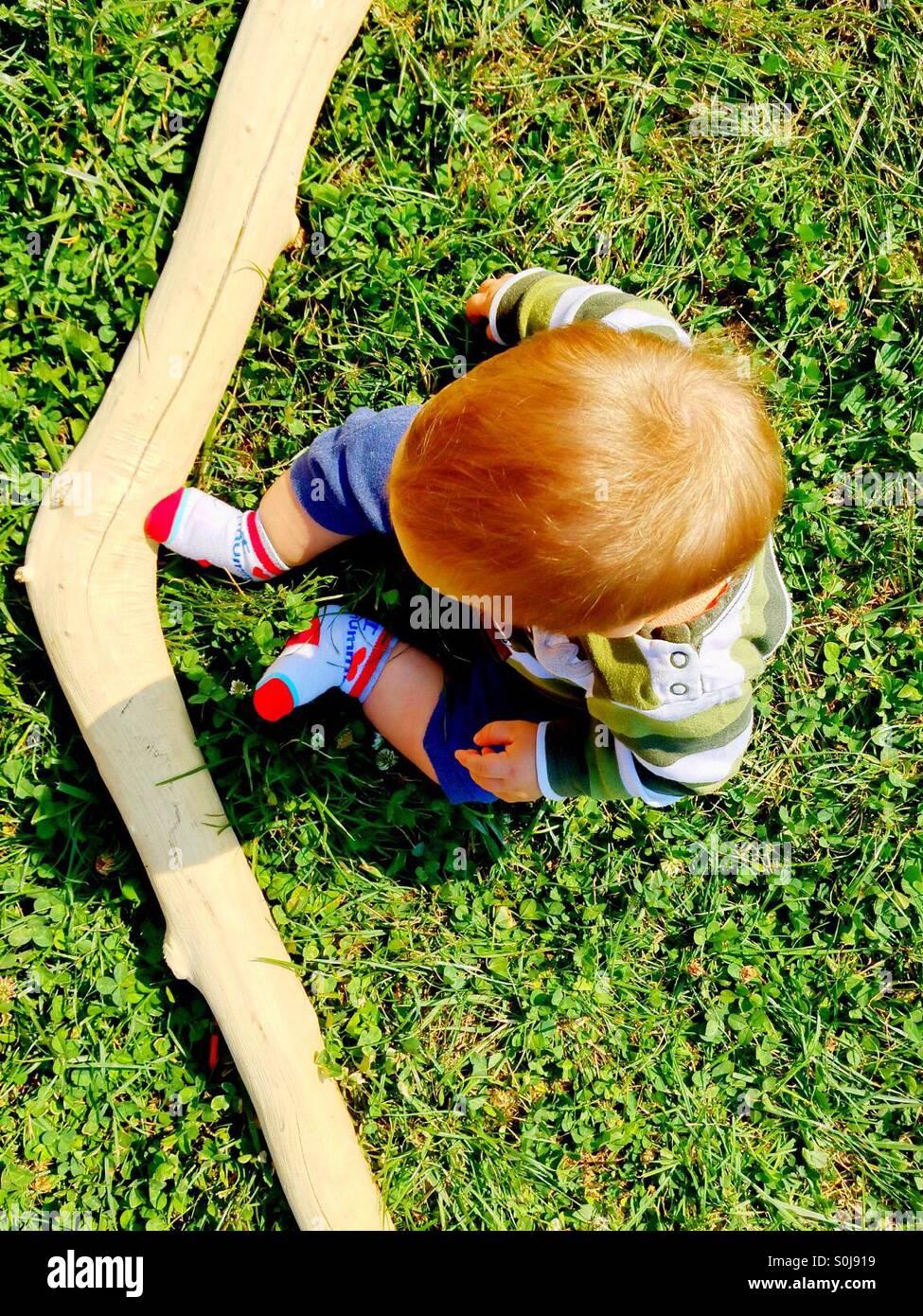 Rothaarige Junge sitzt auf einem grünen Rasen mit einem Stück entrindetes Holz Stockbild