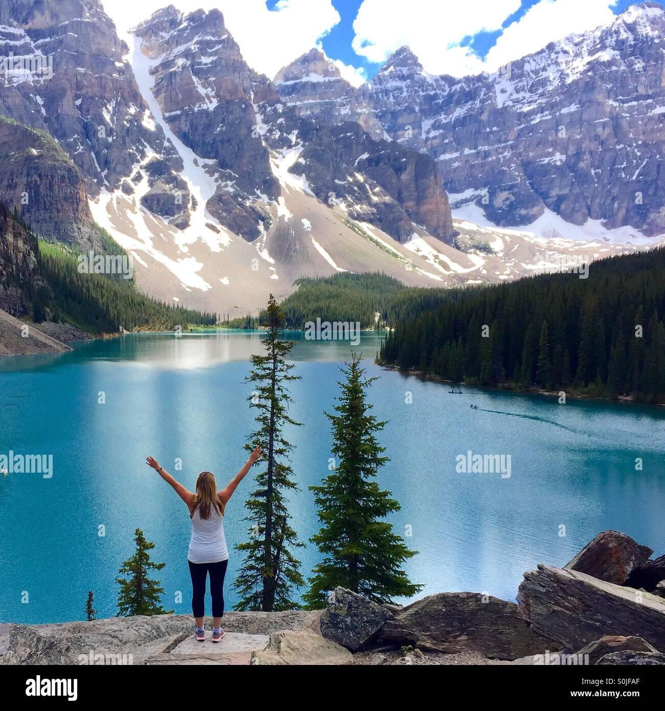Ein Frauen stehen mit ihren Armen über dem Kopf mit Blick auf Moraine Lake in Alberta Kanada Stockbild