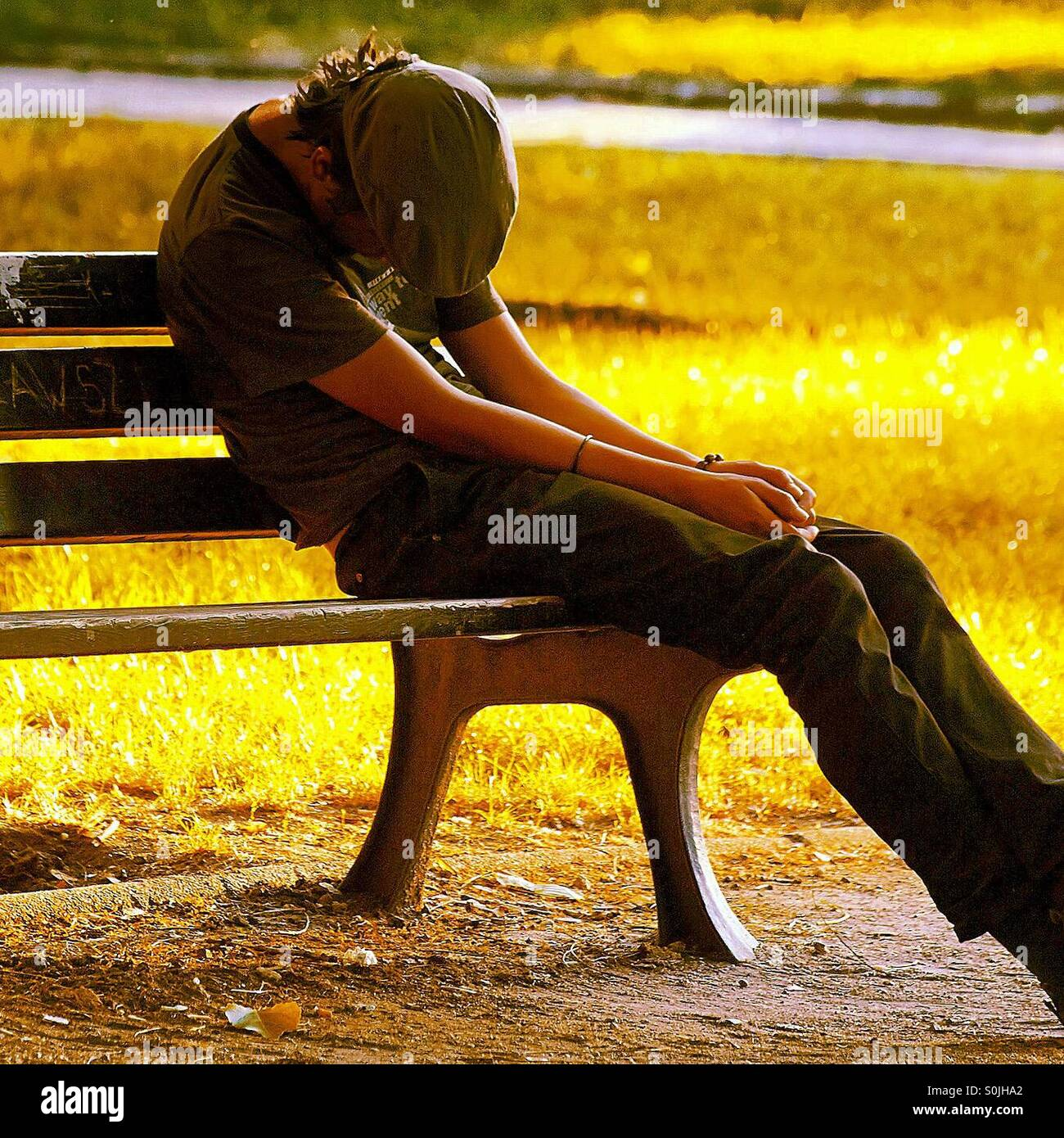 Mann schläft auf Bank Stockbild