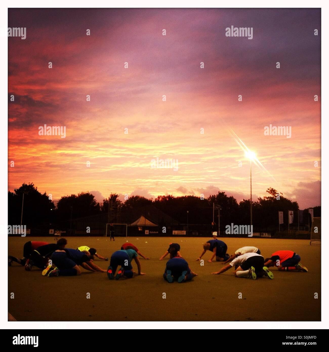 Ein Eishockeyteam Sport Aufwärmen Übung zusammen in einem Kreis mit einem dramatischen rot und lila Sonnenuntergang Stockbild