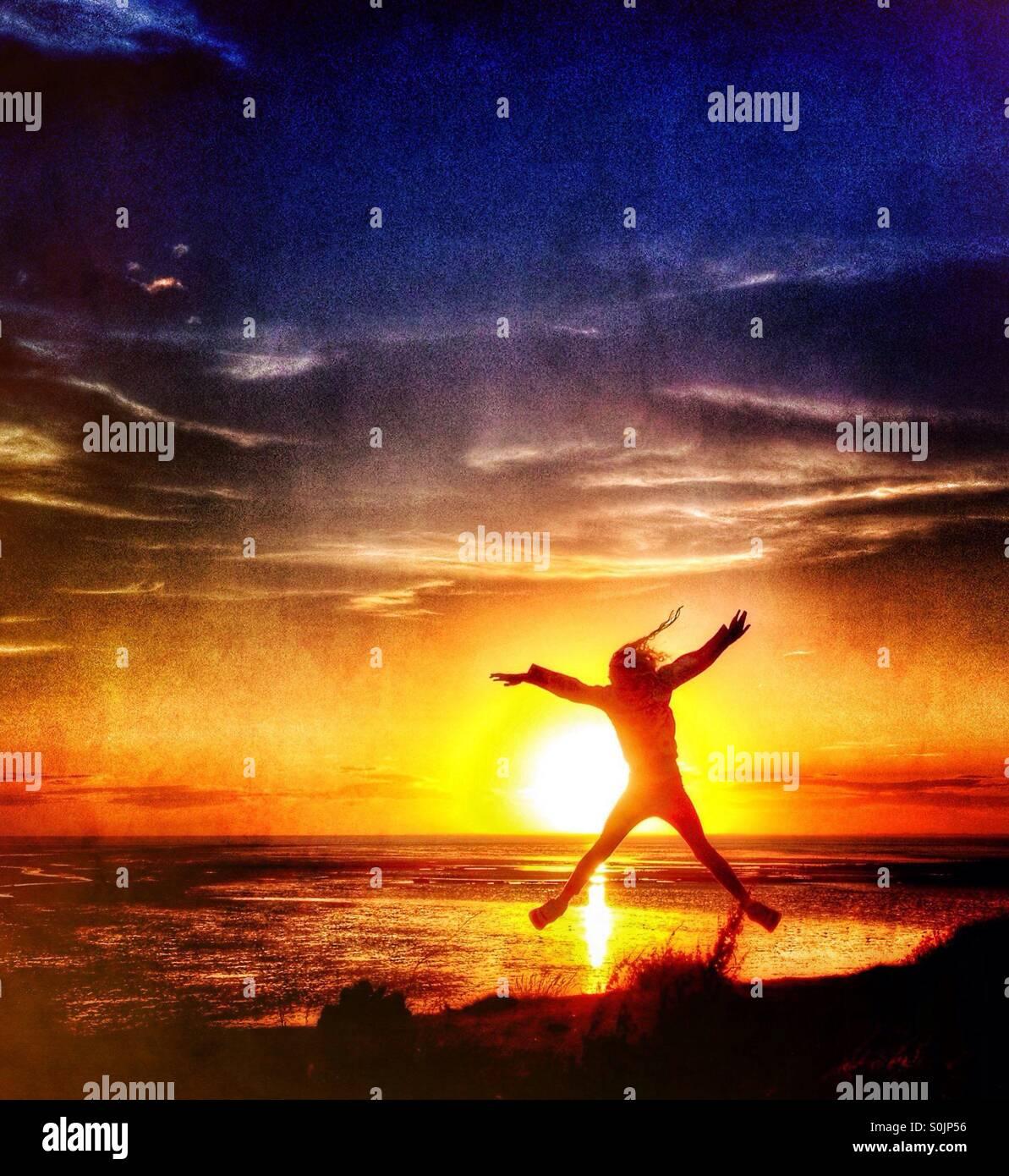 Springen Sie vor Freude gegen die untergehende Sonne über Morecambe Bay Stockbild