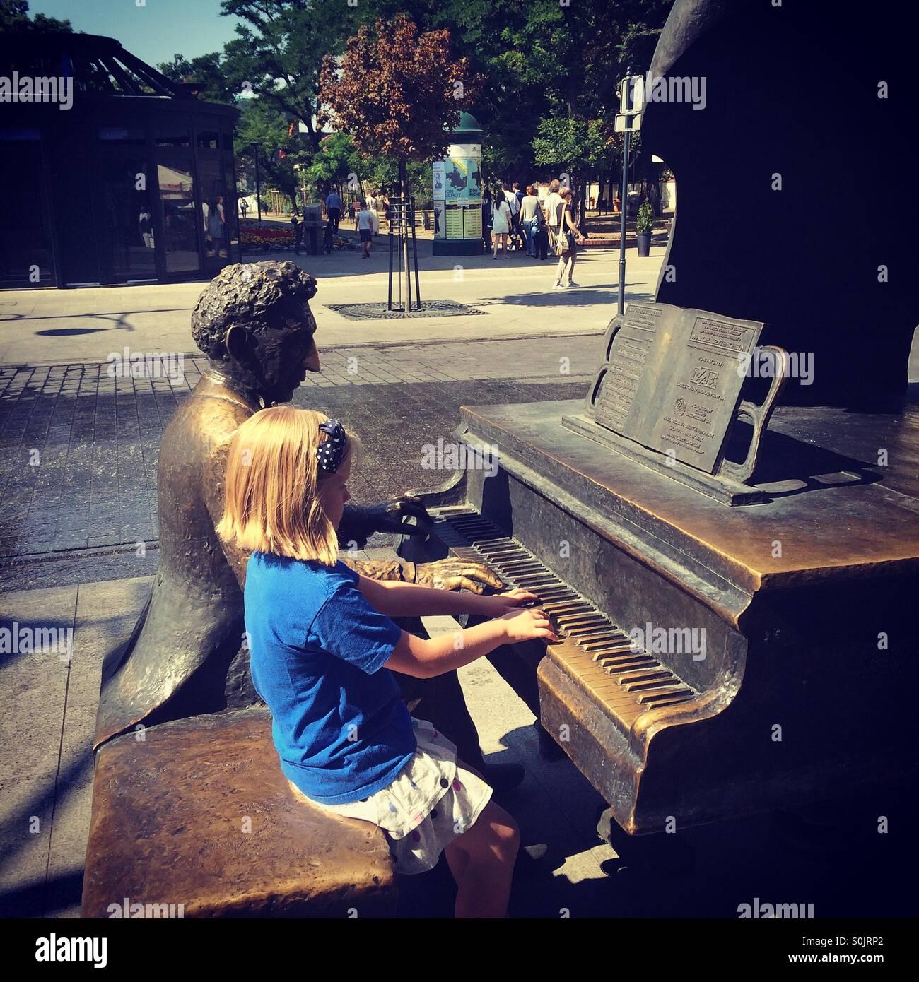 Kleines Mädchen sitzt neben der Statue des berühmten polnischen Komponisten Moniuszko auf Piotrkowska Stockbild