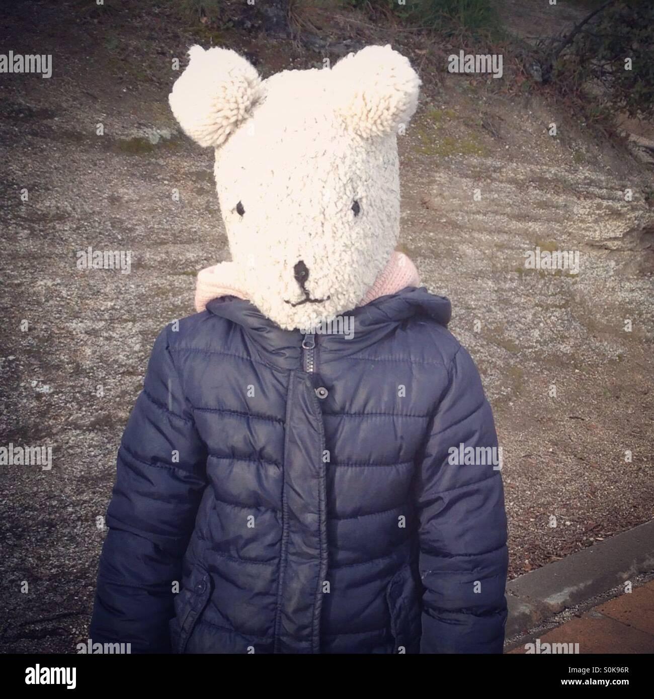 Kind einen Bären Hut umfasst ihr Gesicht Stockbild