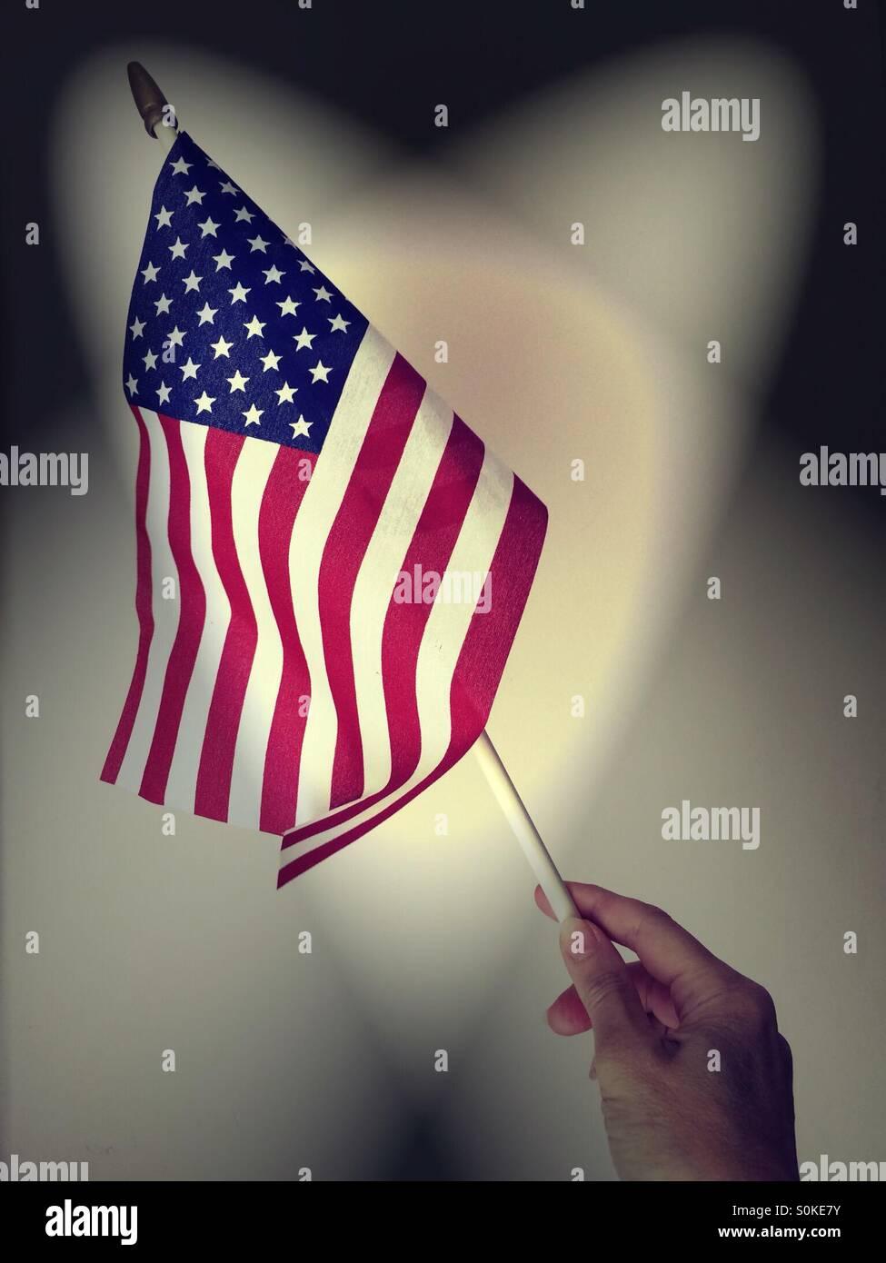 Scheinwerfer auf amerikanische Flagge mit der hand gehalten Stockbild