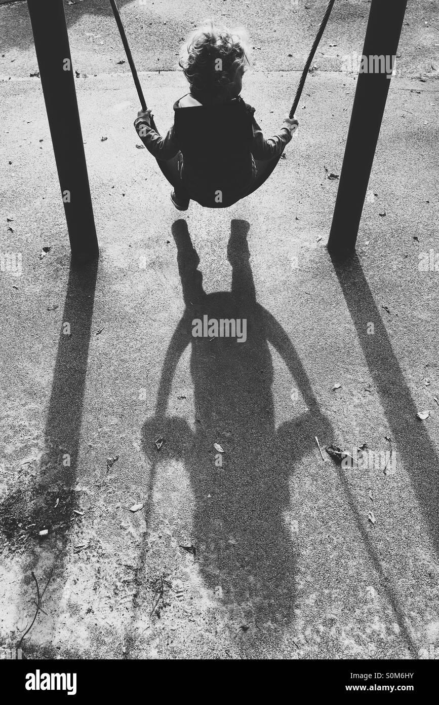Junge auf Schaukel mit langen Schatten Stockbild