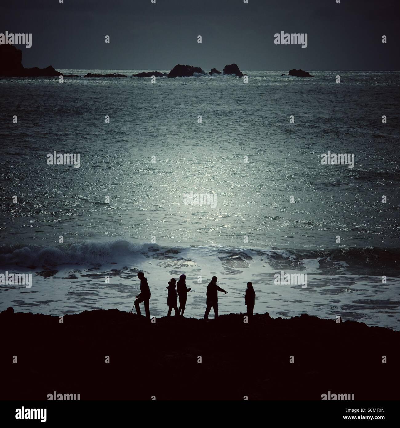 Fünf Silhouetten auf ein Abenteuer am Meer. Der Mondschein Ozean hinter ihnen. Stockbild