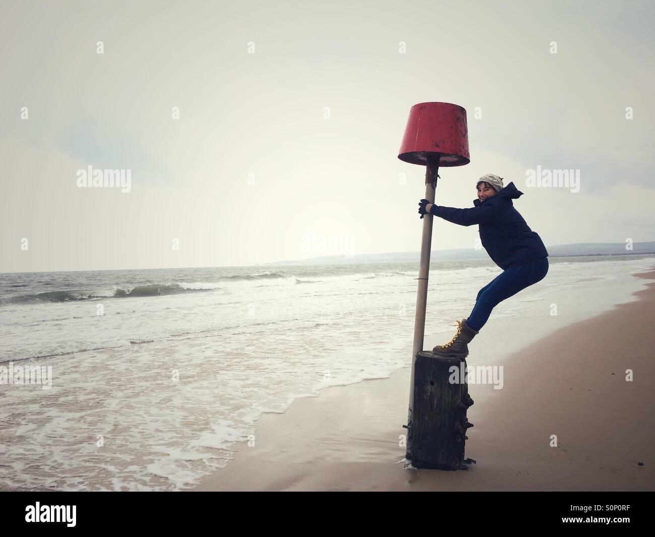 Frau mit Spaß balancieren auf Markierungsboje auf Dorset Strand im Winter Stockbild