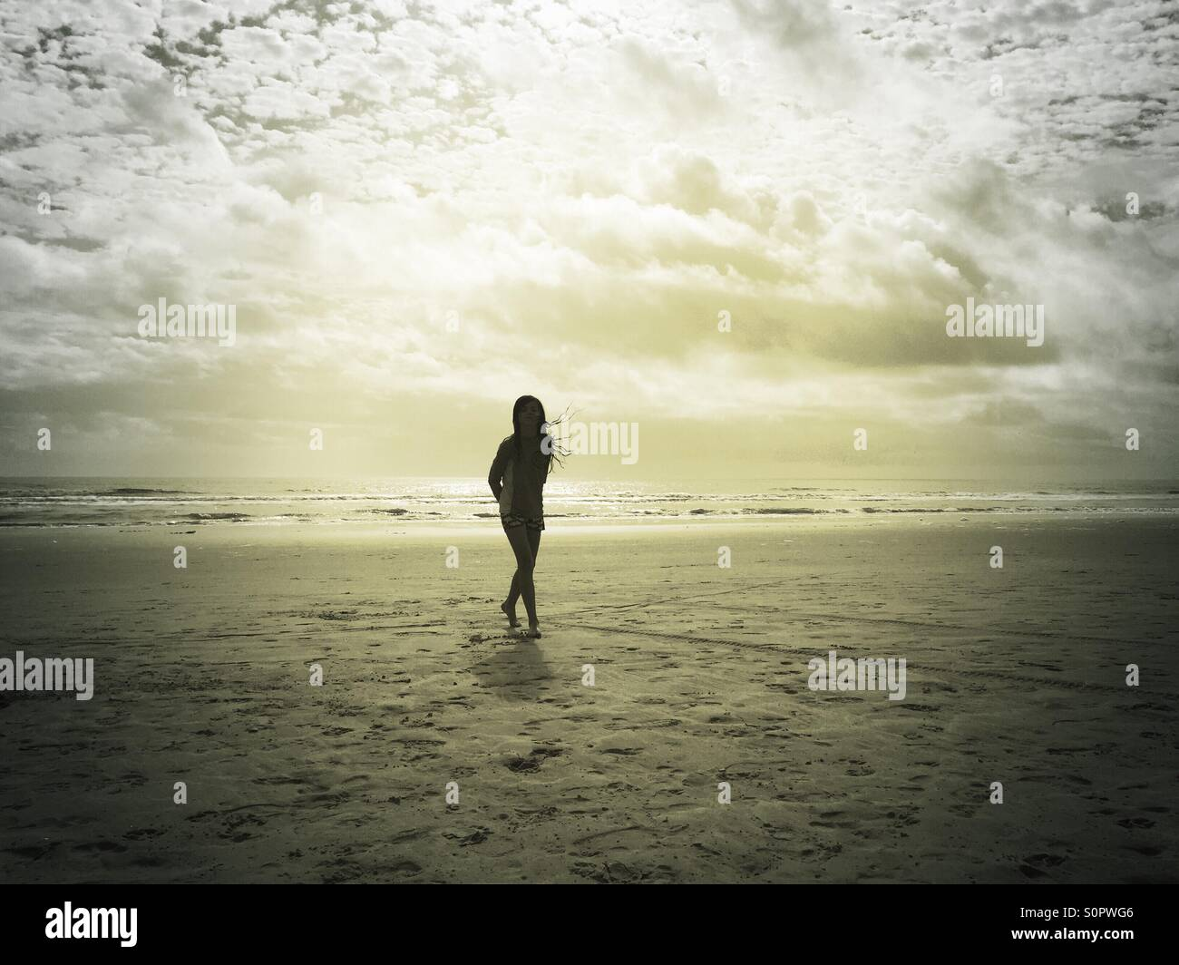 Ein Mädchen tanzt am Strand unter einem Gewitterhimmel. Stockbild