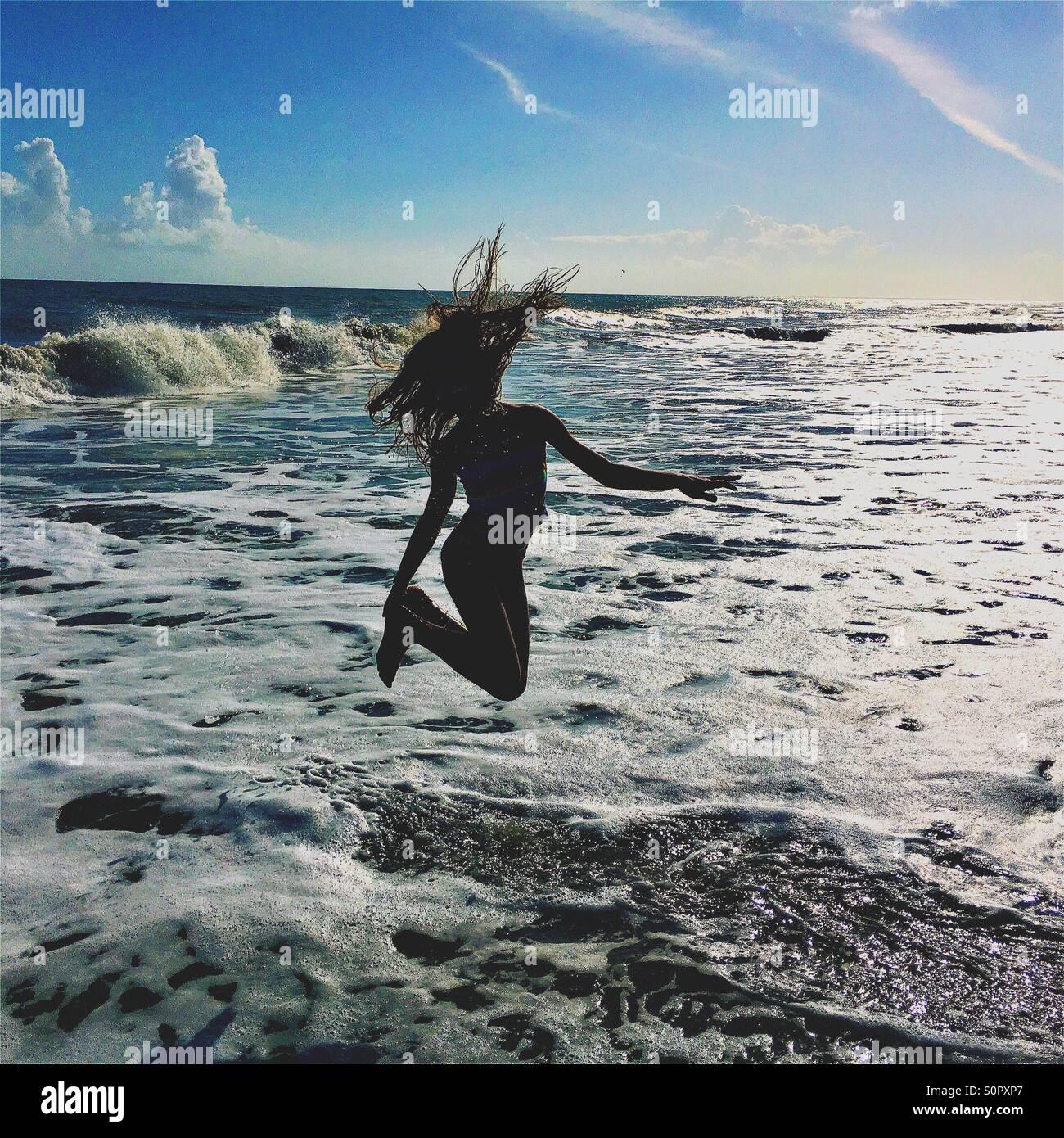 Mädchen in den Wellen des Ozeans springen Stockbild