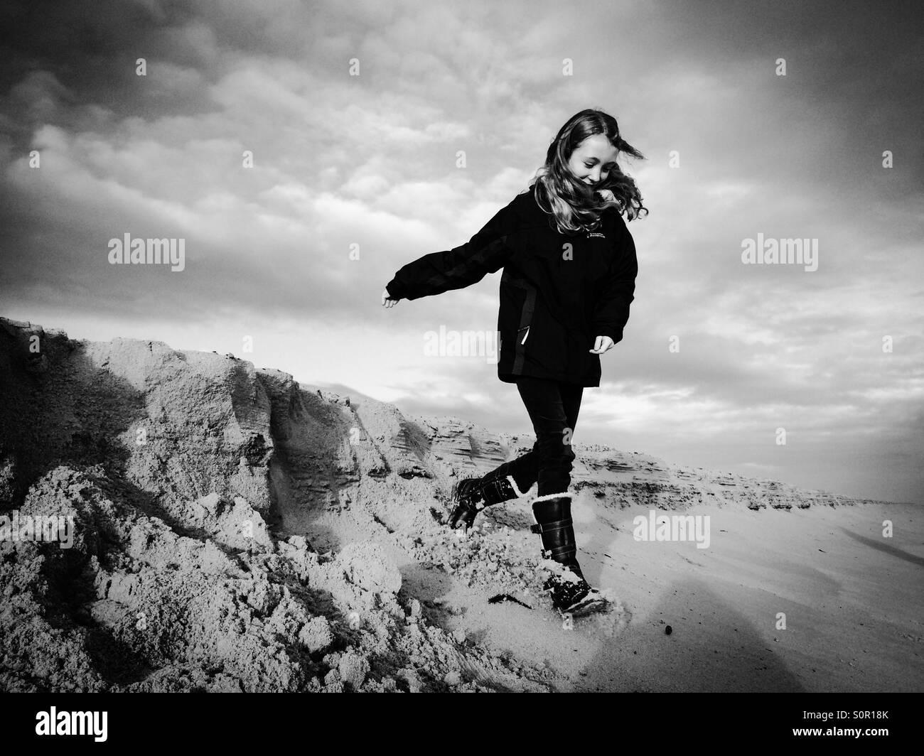 Ein 11 Jahre altes Mädchen, die Spaß am Strand von Winterton in Norfolk Stockbild