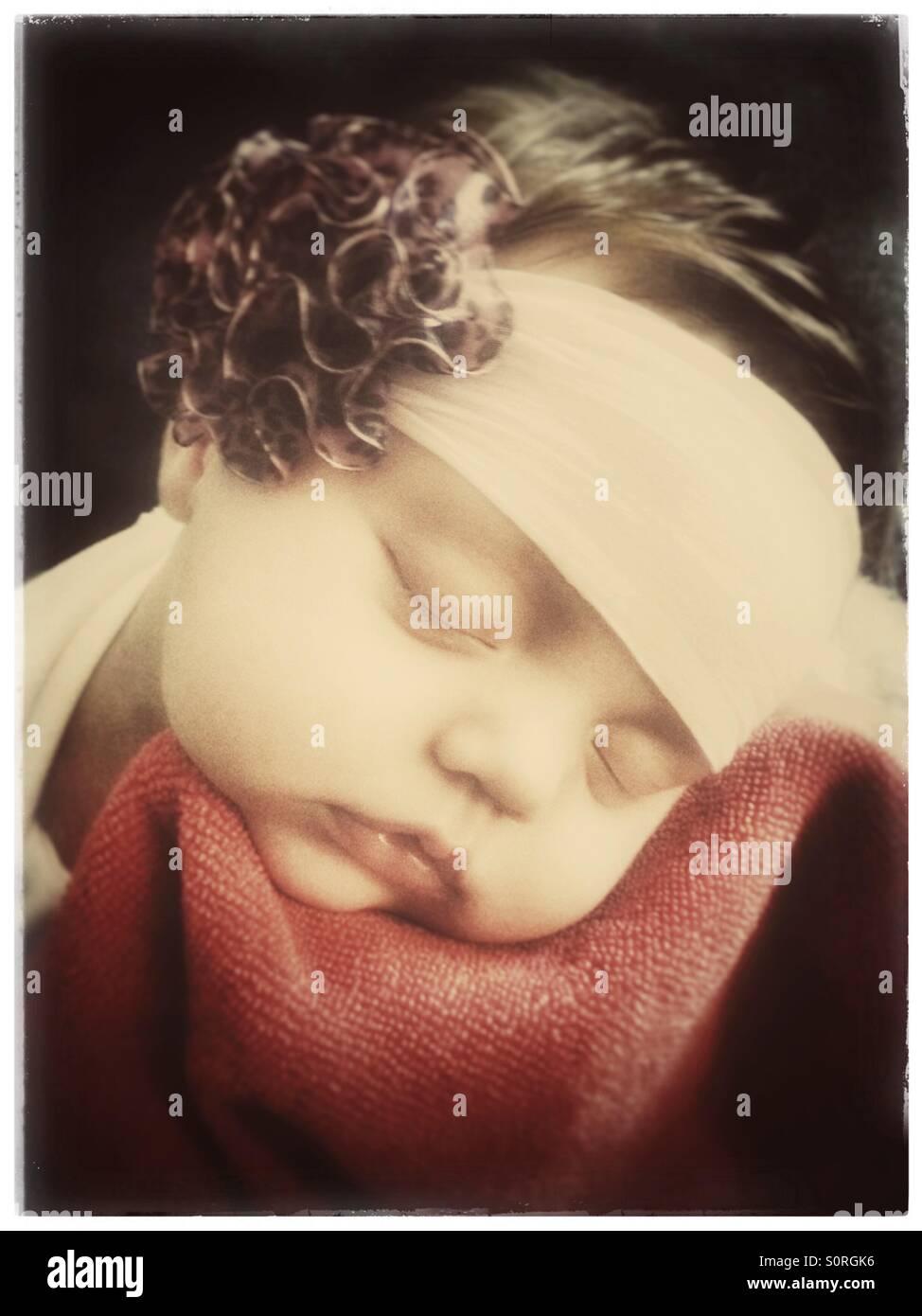 Schlafendes Baby trägt eine Stirnband mit einer Blume Stockbild