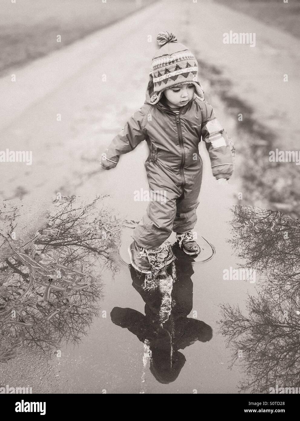 Kleiner Junge tanzen im Regen Stockbild