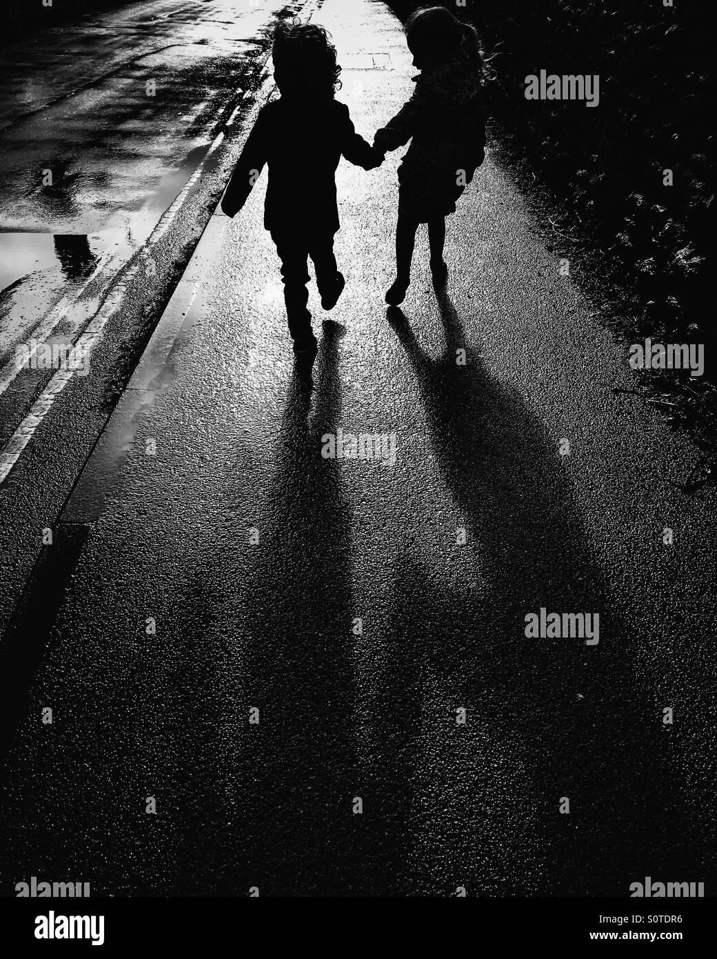 Silhouette von zwei Kinder halten sich an den Händen Stockbild