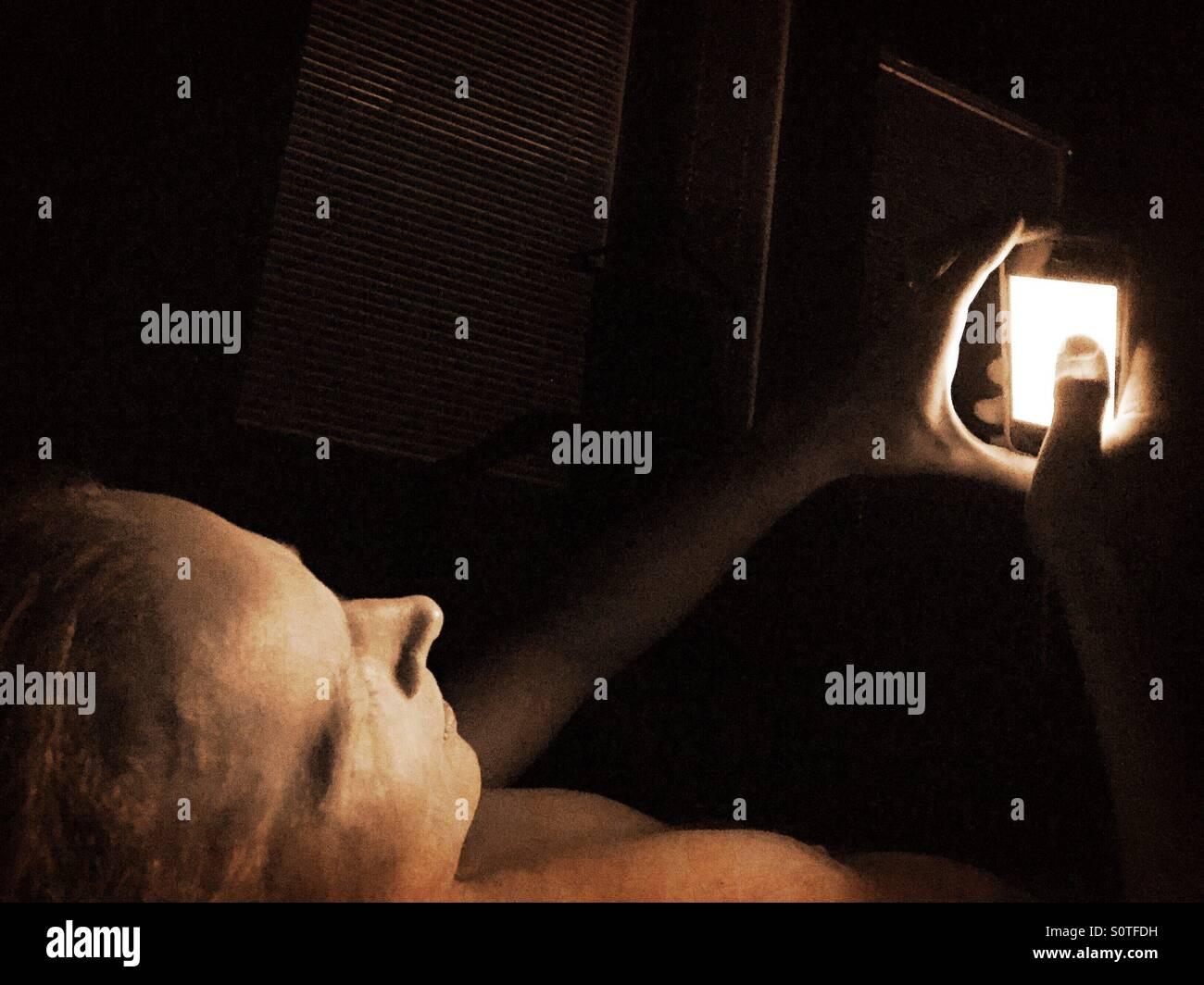 Ein Mann mit einem iPhone im dunklen Schlafzimmer Stockbild