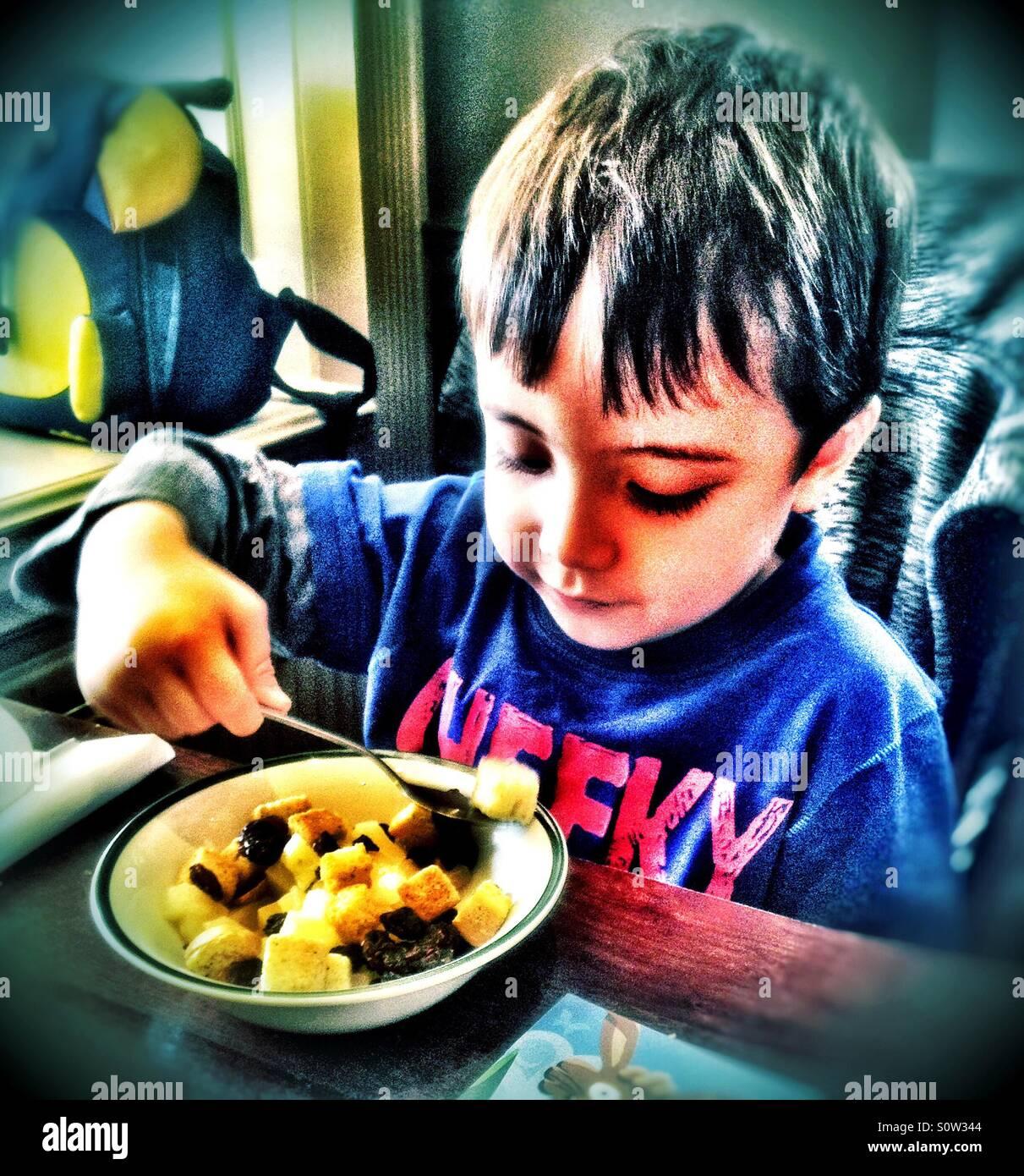 Ein kleiner Junge, einen gemischten Salat, Ananas, Mais, Rosinen und Croutons zu essen. Stockbild