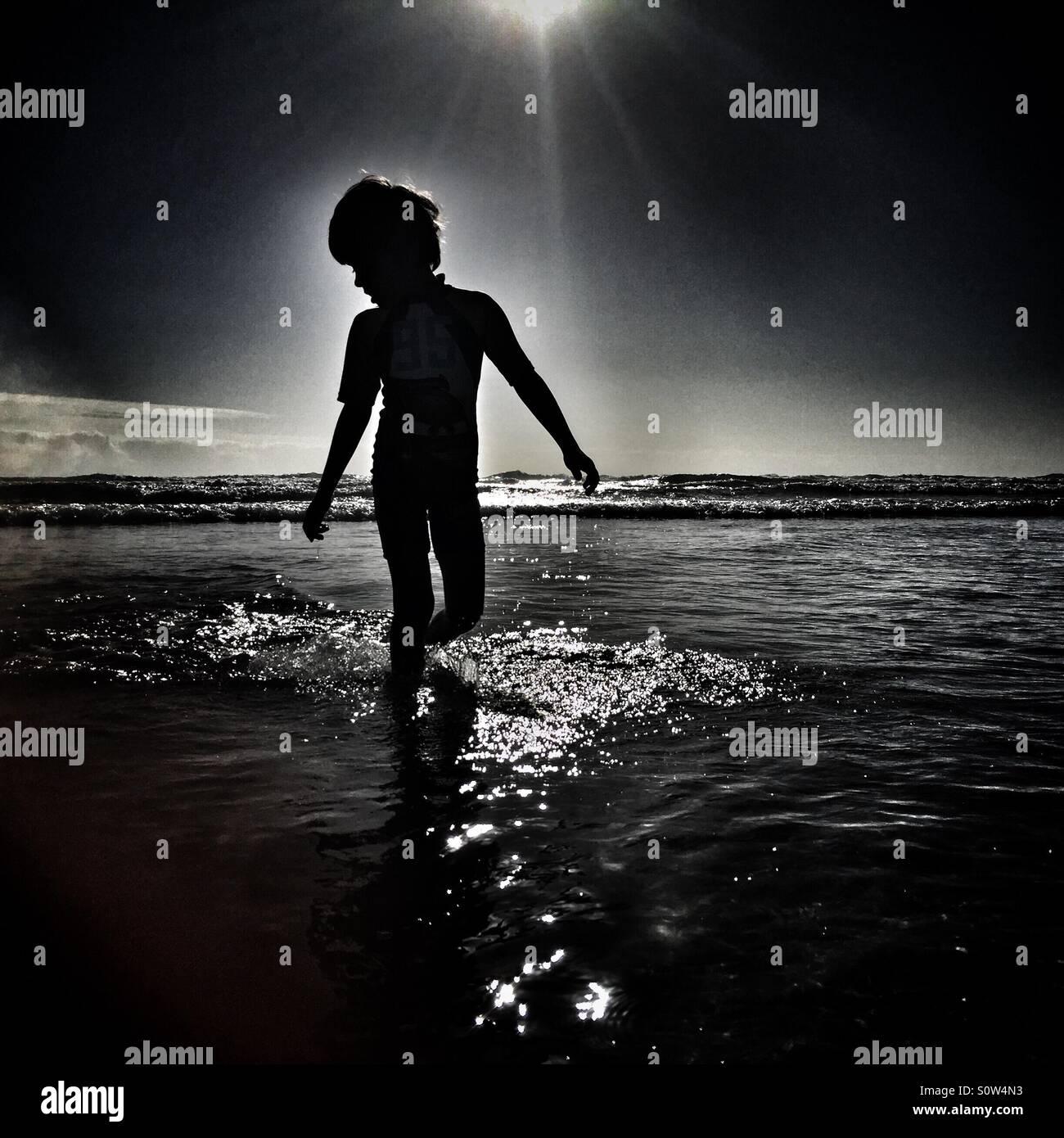 Boy am Strand silhouette Stockbild