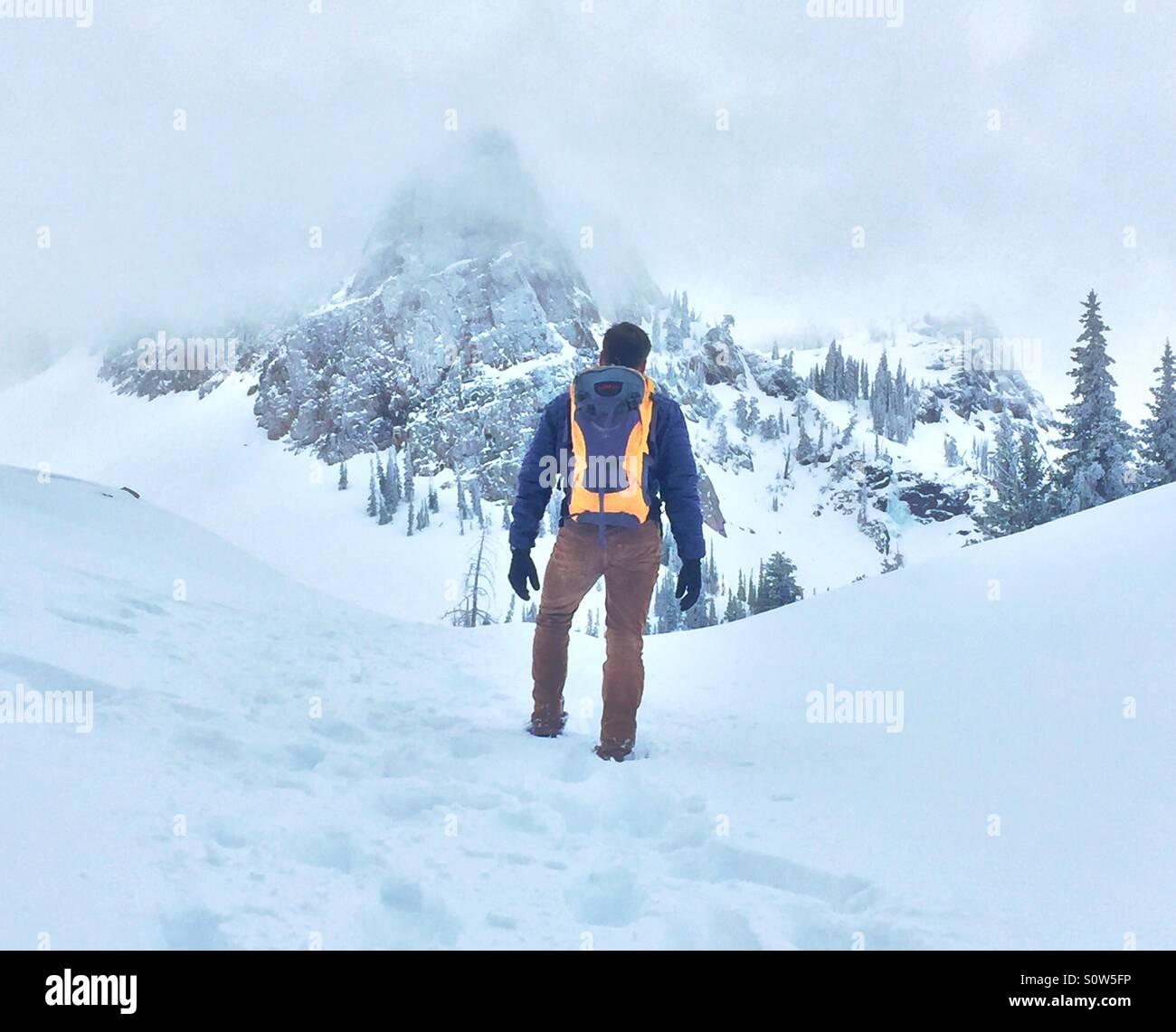 Ein Mann Wanderungen bis zu einem Berggipfel im Schnee bedeckten Utah. Stockbild