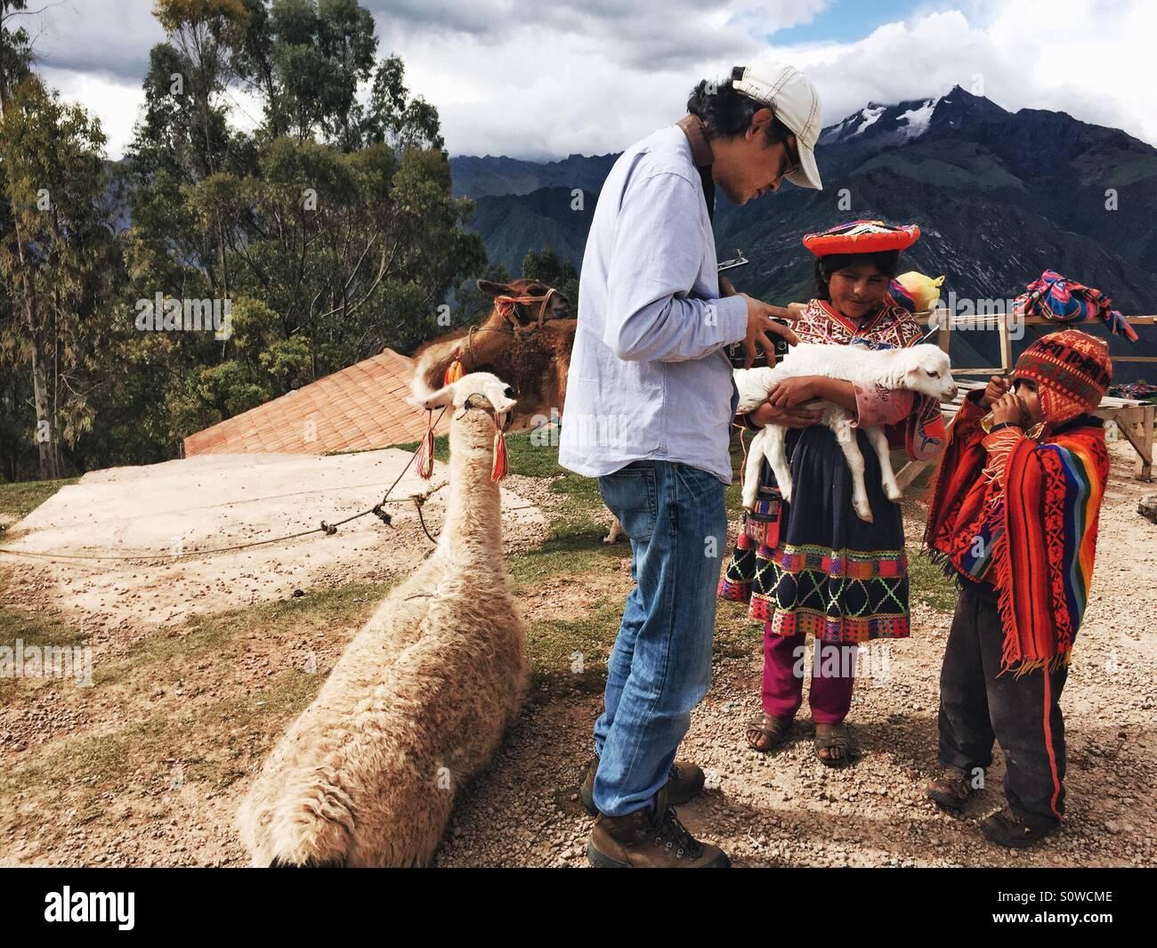 Mann Fotografieren Kinder in traditioneller Kleidung in Peru Stockbild
