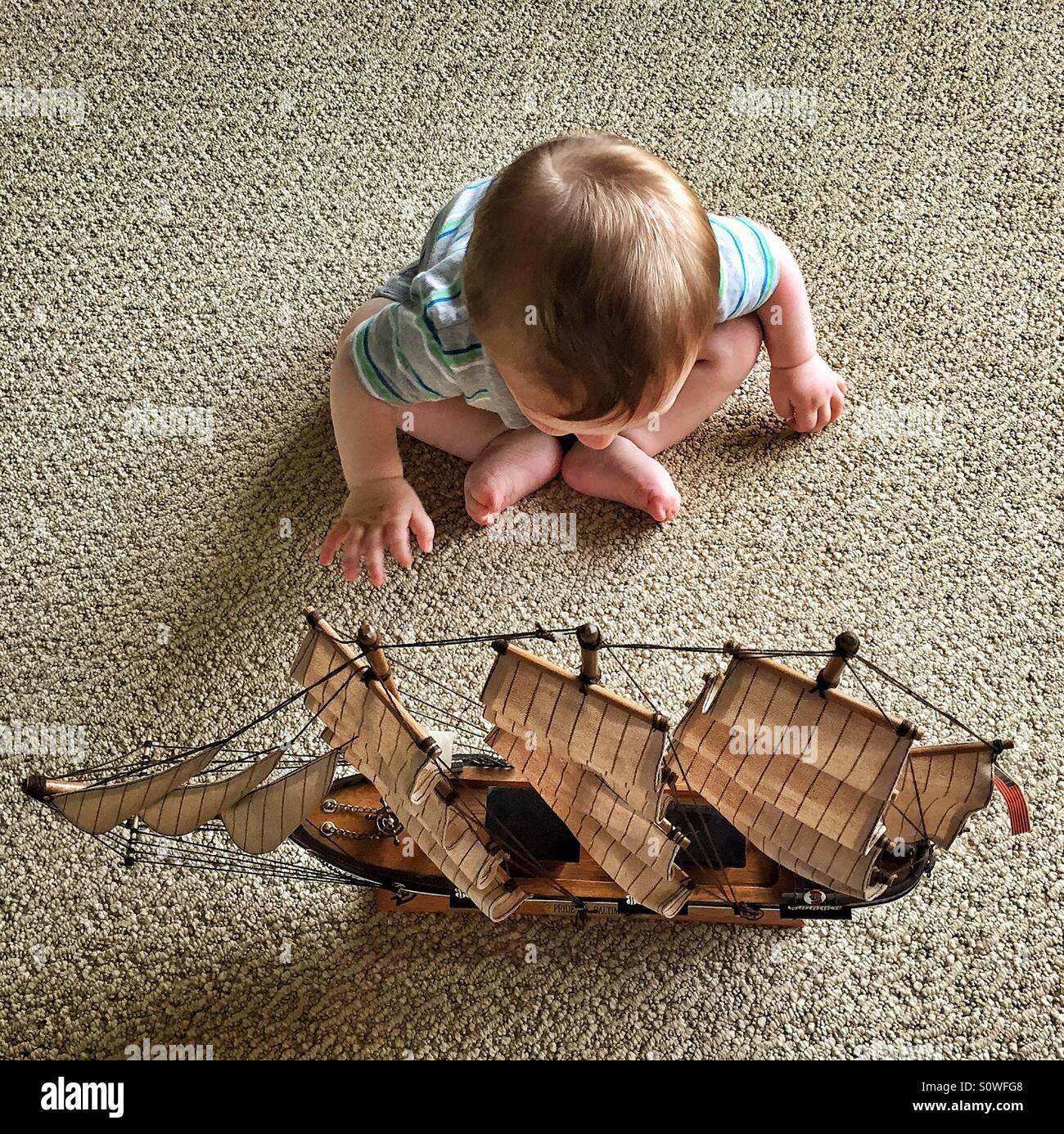 Baby für ein Modellschiff auf dem Boden sitzend zu erreichen Stockbild