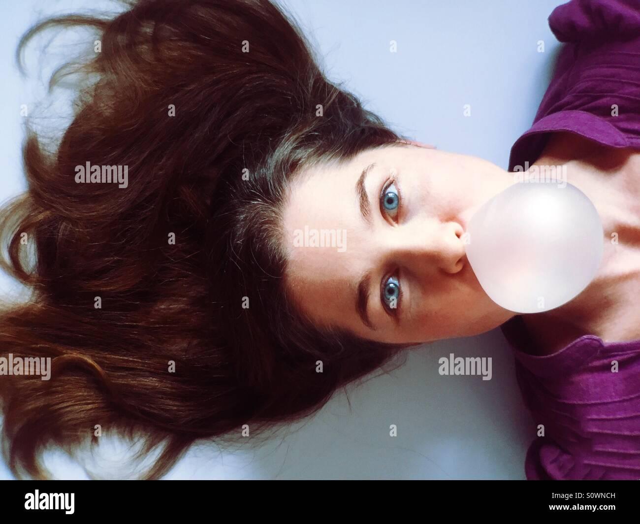 Frau bläst eine Kaugummi-Blase Stockbild