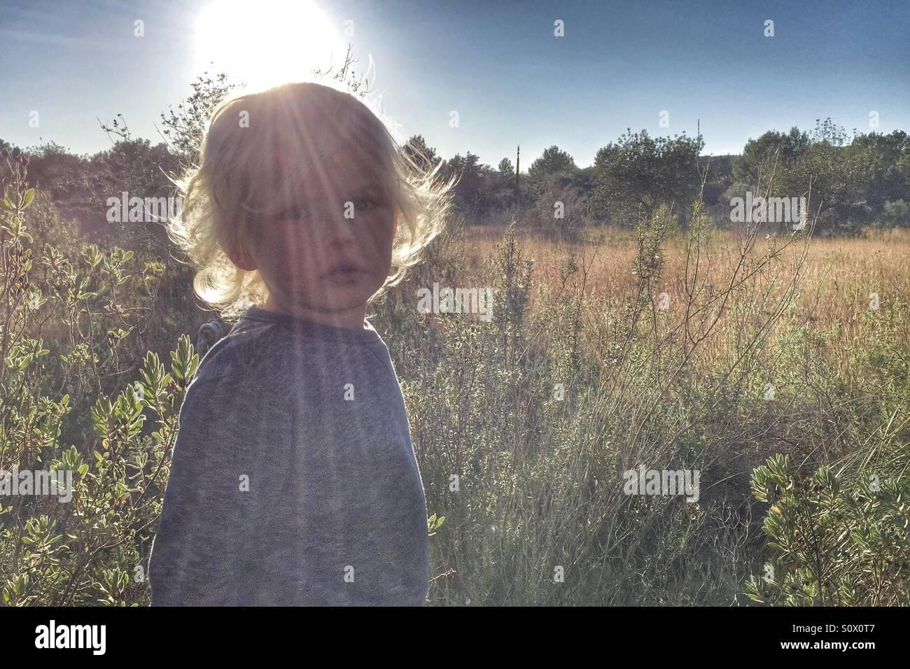 Junge in einem sonnigen Bereich Stockbild