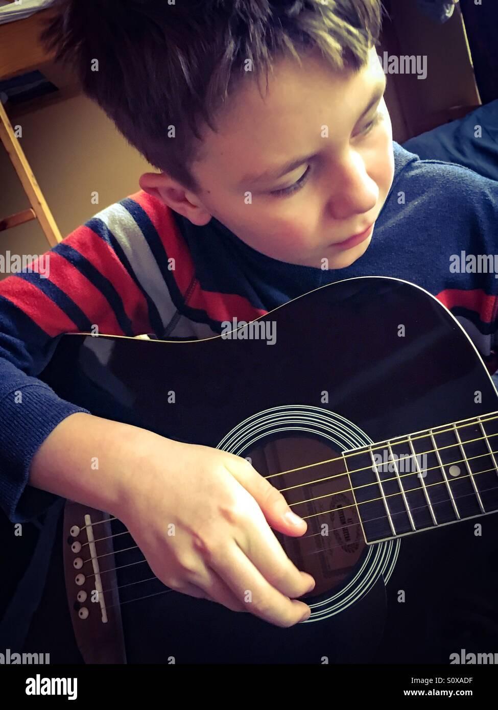 11 Jahre alter Junge seine Gitarre am Morgen Stockbild
